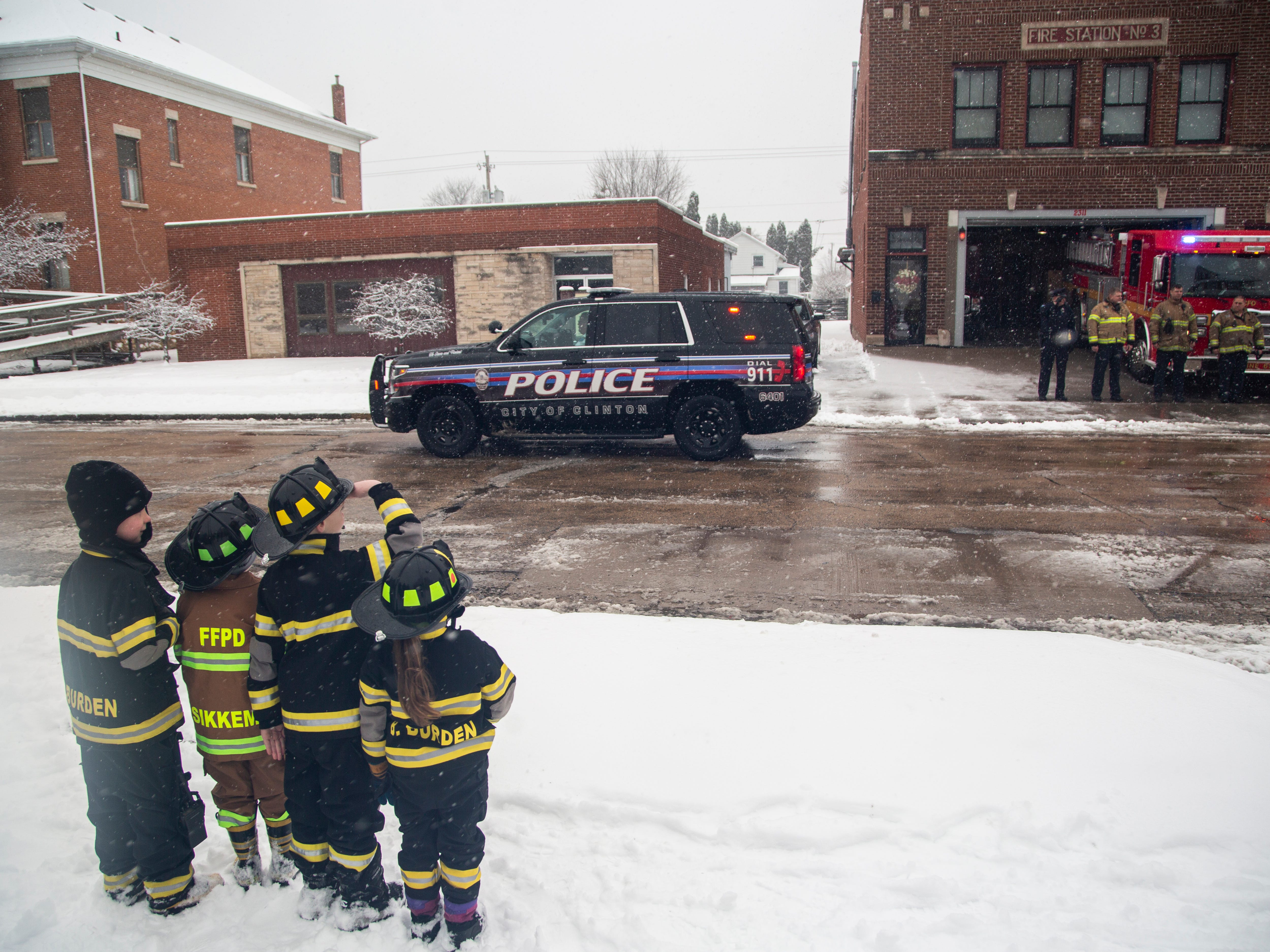 Kinnick Burden, 6, Jackson Sikkema, 5, Jax Stage, 6, and Brynlee Burden, 4, look on as vehicles drive in a procession past Fire Station No. 3 after the public memorial service for Lt. Eric Hosette on Saturday, Jan. 12, 2019, along 2nd Street in Clinton, Iowa.