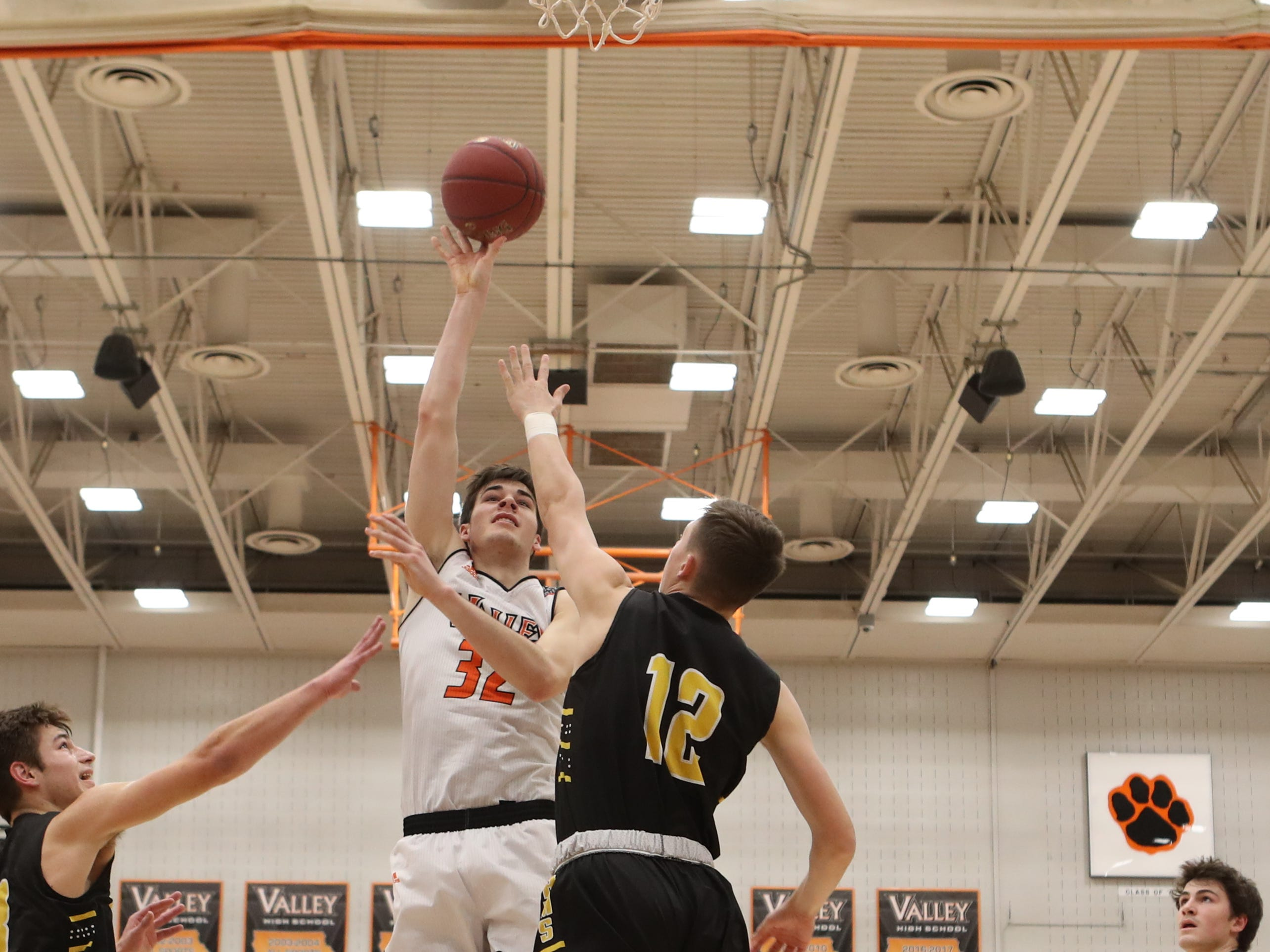 Valley Tigers' Will Berg (32) shoots and scores over the top of Southeast Polk Rams' Fred Johnson (12) during a boys basketball game at Valley High School on Jan. 11, 2019.