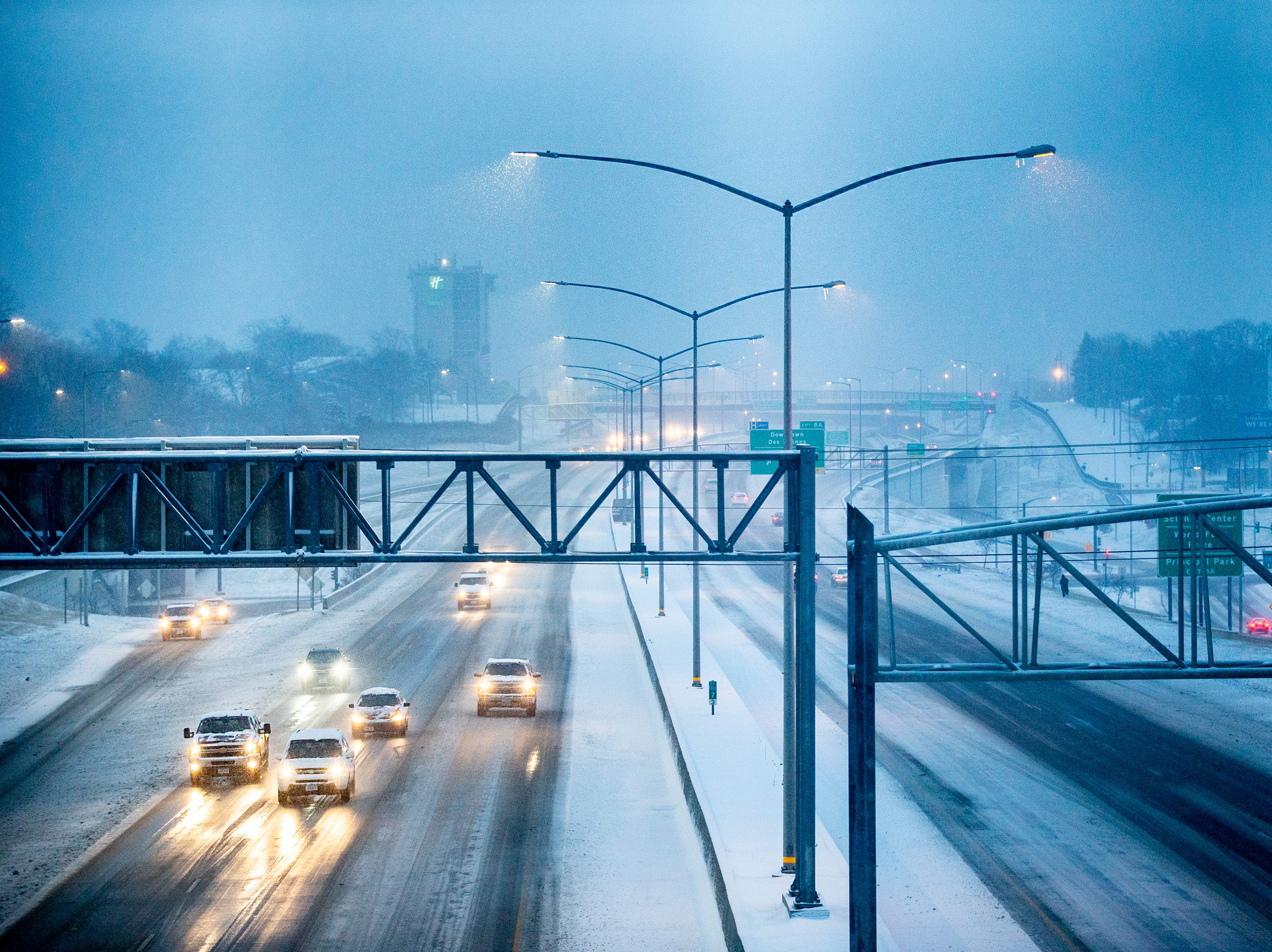 Drivers make their way down a partially snow covered Interstate 235 through downtown Des Moines just before dawn on Saturday, Jan. 12, 2019.
