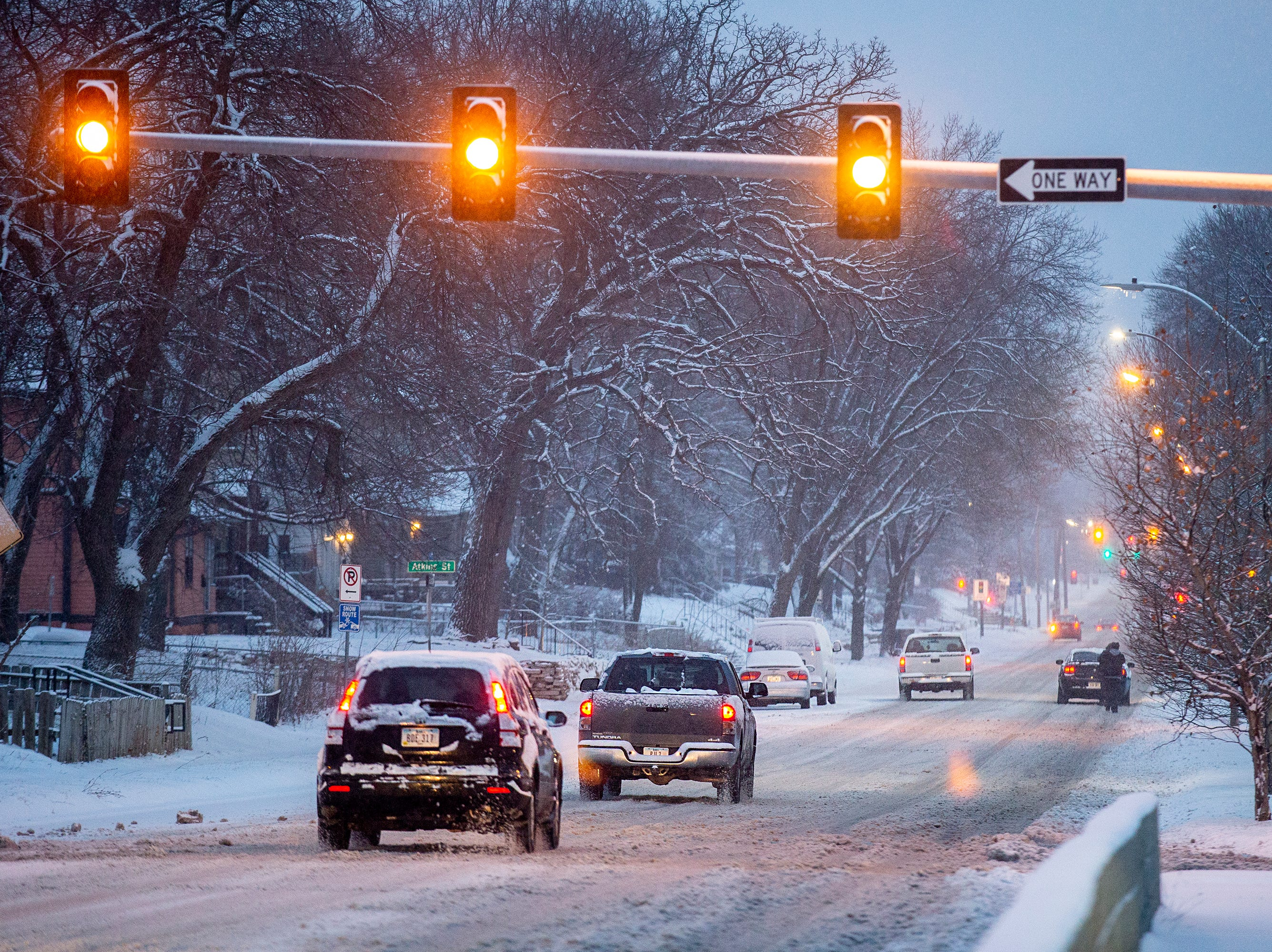 Drivers navigate snow covered roads just before dawn on Saturday, Jan. 12, 2019, in Des Moines.