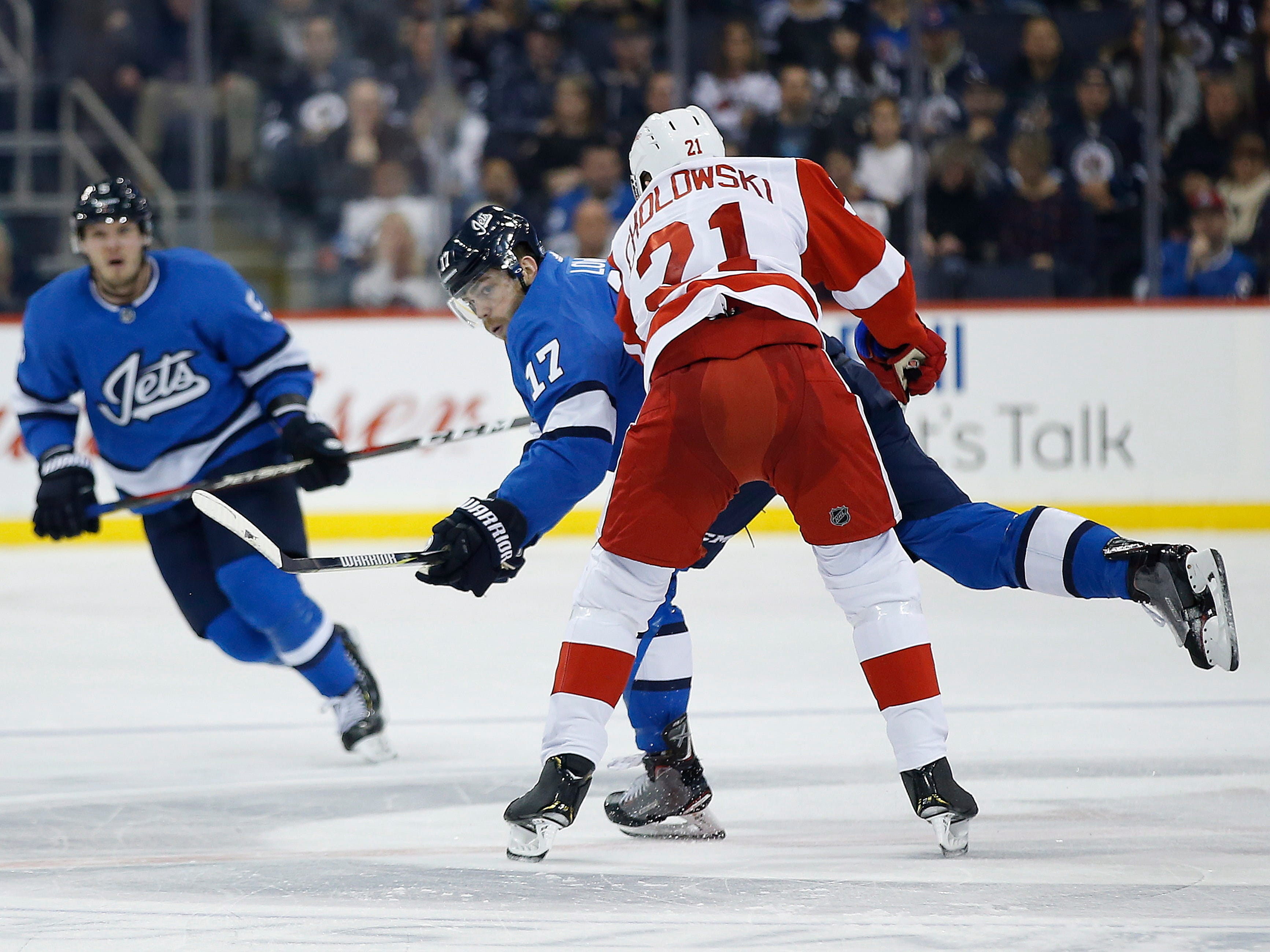 Winnipeg Jets' Adam Lowry (17) dumps the puck in as Detroit Red Wings' Dennis Cholowski defends during the second period Friday, Jan. 11, 2019, in Winnipeg, Manitoba.