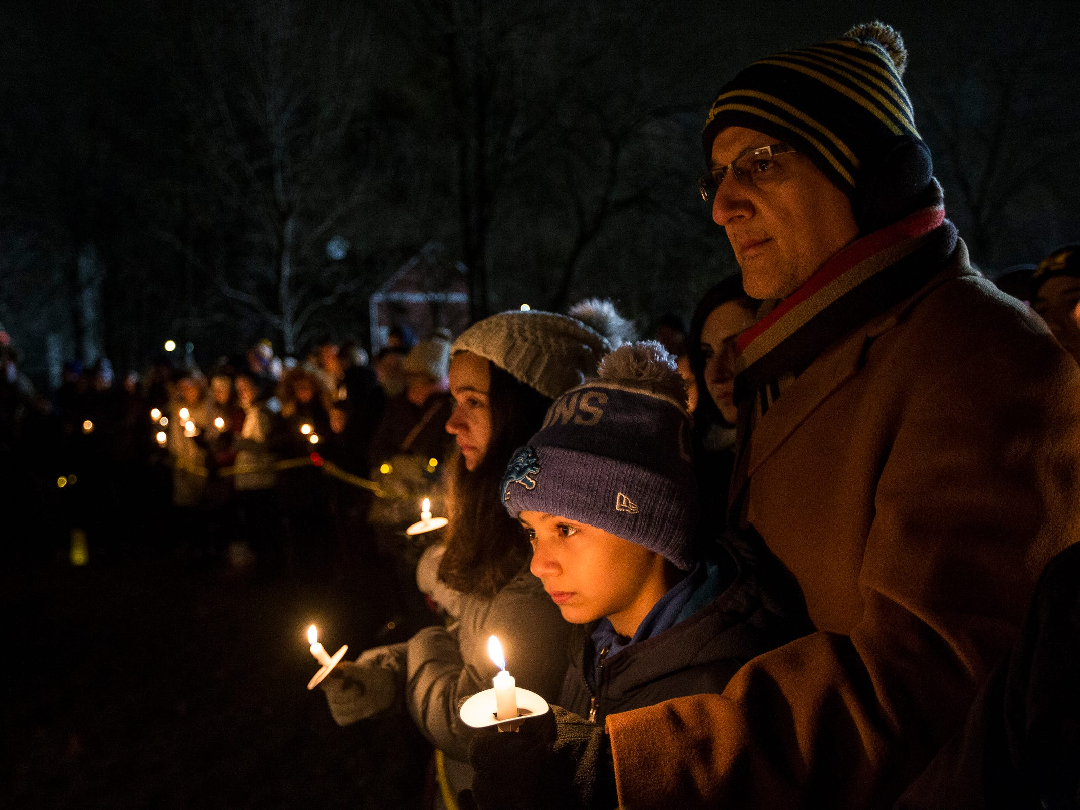 Essam Khraizat and his son Zane 11, remember their friends in the Abbas family during a candlelight vigil at the Ford Field Park in Northville Friday, Jan. 11, 2019.