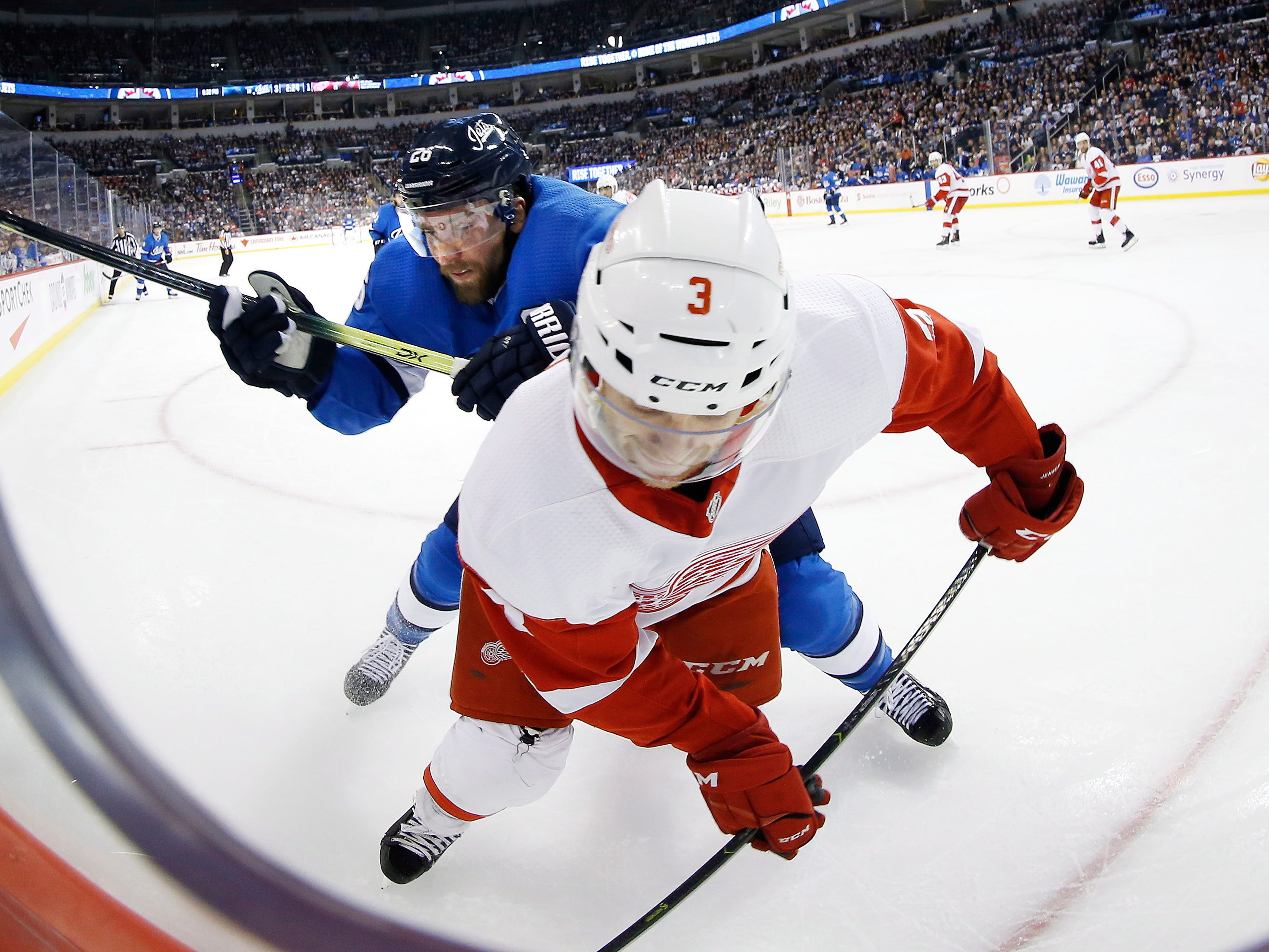Winnipeg Jets' Jack Roslovic checks Detroit Red Wings' Nick Jensen during the second period Friday, Jan. 11, 2019, in Winnipeg, Manitoba.