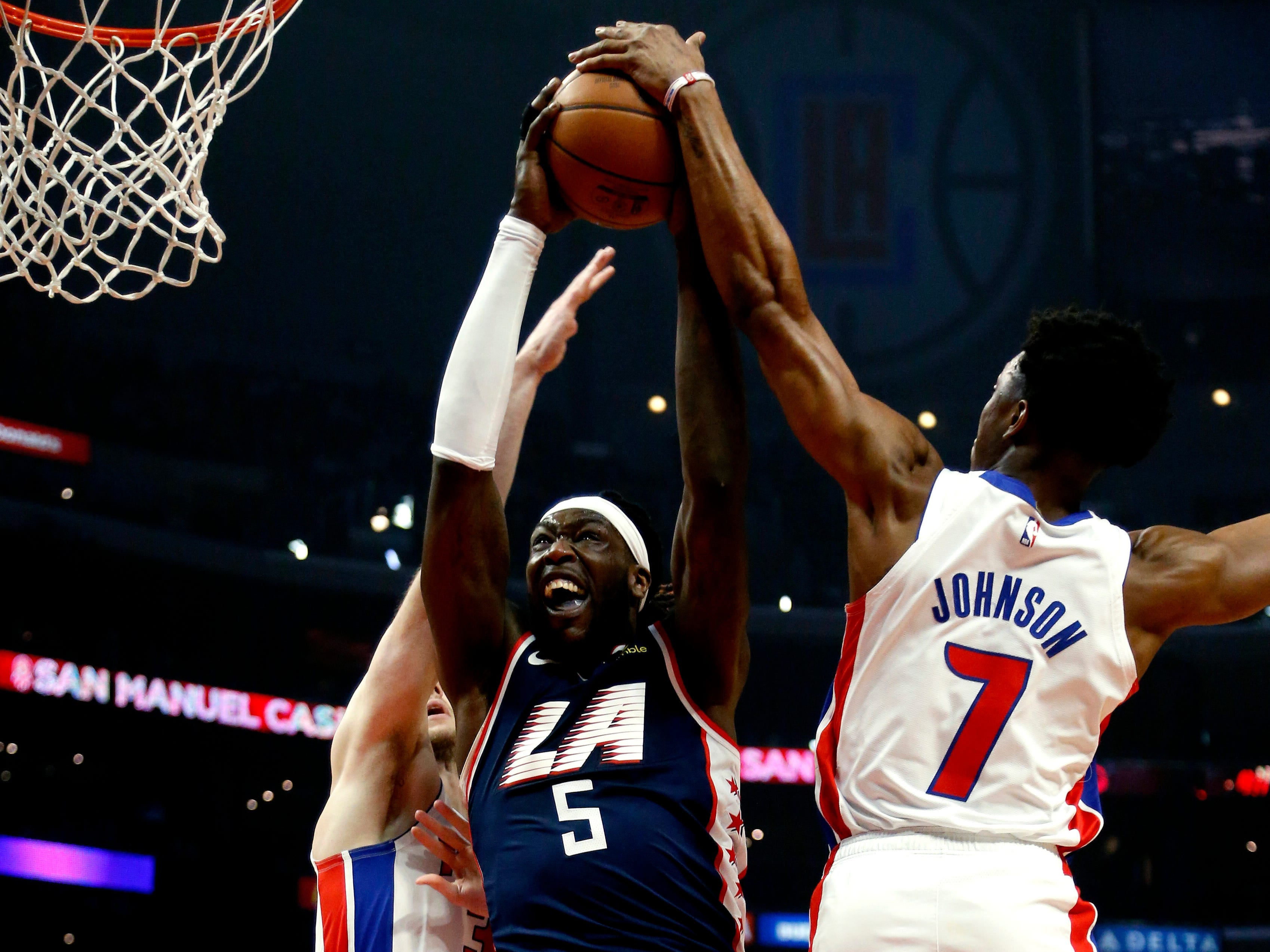 Clippers center Montrezl Harrell goes up to the basket while defended by Pistons forwards Jon Leuer, left, and Stanley Johnson during the first half on Jan. 12, 2019, in Los Angeles.