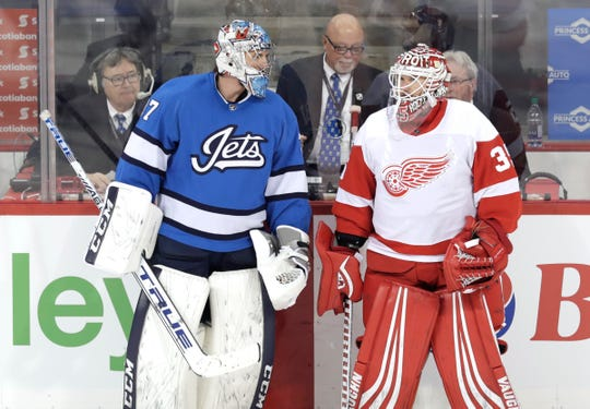 Jets goaltender Connor Hellebuyck talks with Wings goaltender Jimmy Howard during warmups at Bell MTS Place, Jan. 11.