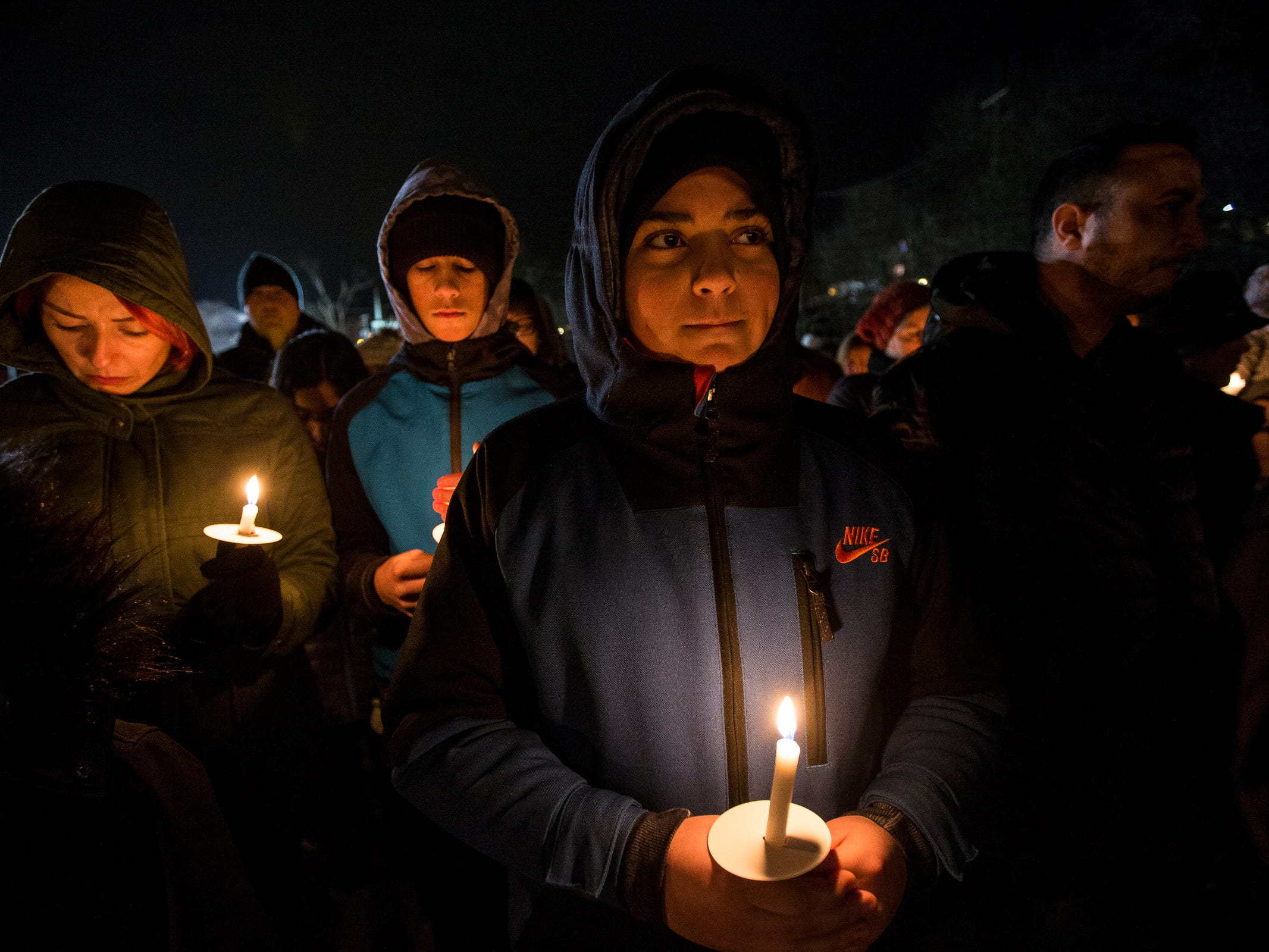Adham Elmallah, 13, center, with his brother Nabil 15, and mother Navila, left, all of Dearborn remember their friends in the Abbas family during a candlelight vigil at the Ford Field Park in Northville Friday, Jan. 11, 2019.