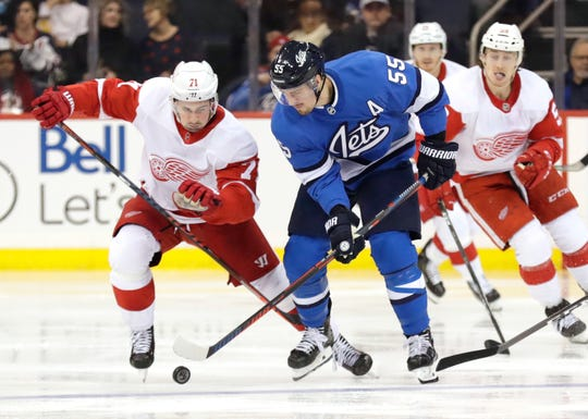 Wings center Dylan Larkin chases down Jets center Mark Scheifele in the first period Friday.