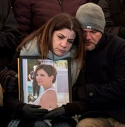 Rana Abbas Taylor holds a photo of her sister Rima Abbas, while being comforted by her husband Tom during a candlelight vigil for the Abbas family at the Ford Field Park in Northville Friday, Jan. 11, 2019.