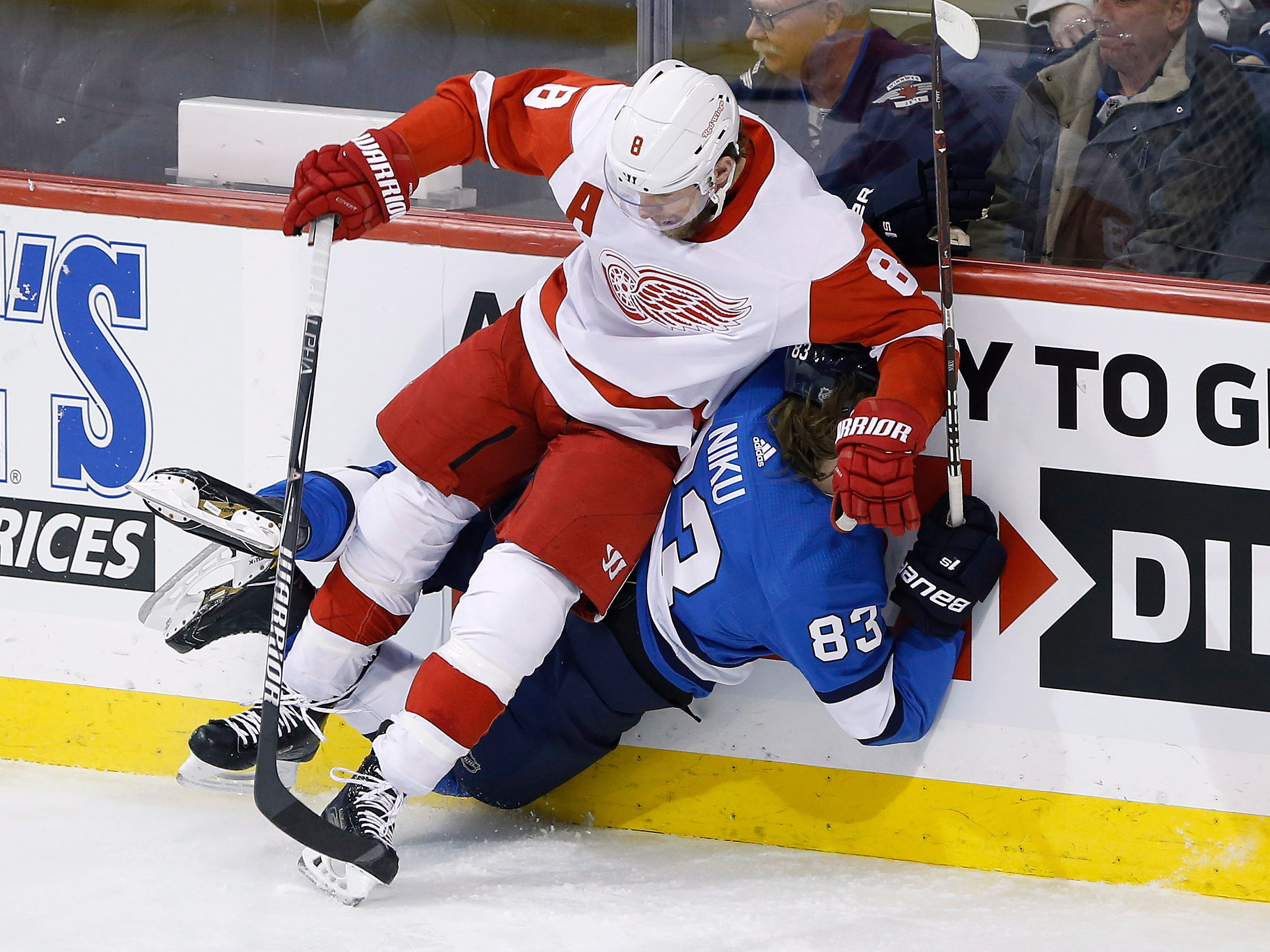 Winnipeg Jets' Sami Niku is checked by Detroit Red Wings' Justin Abdelkader during the first period Friday, Jan. 11, 2019, in Winnipeg, Manitoba.