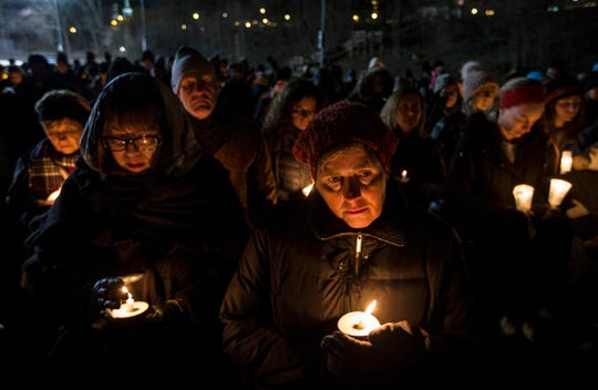 Beth Tryon of West Bloomfield, center, and Renee Fein of Southfield, remember their friends from the Abbas family during a candlelight vigil at the Ford Field Park in Northville Friday, Jan. 11, 2019.