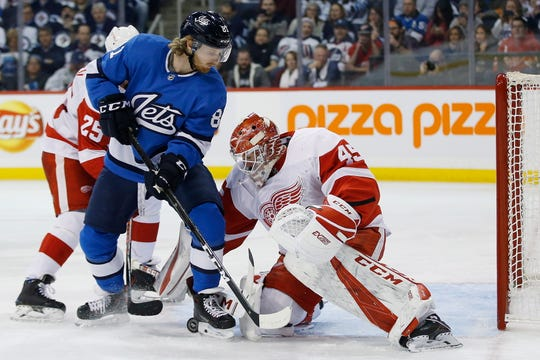 Wings goaltender Jonathan Bernier jumps on a loose puck as Jets' Kyle Connor applies pressure and Wings' Mike Green defends during the second period Friday.
