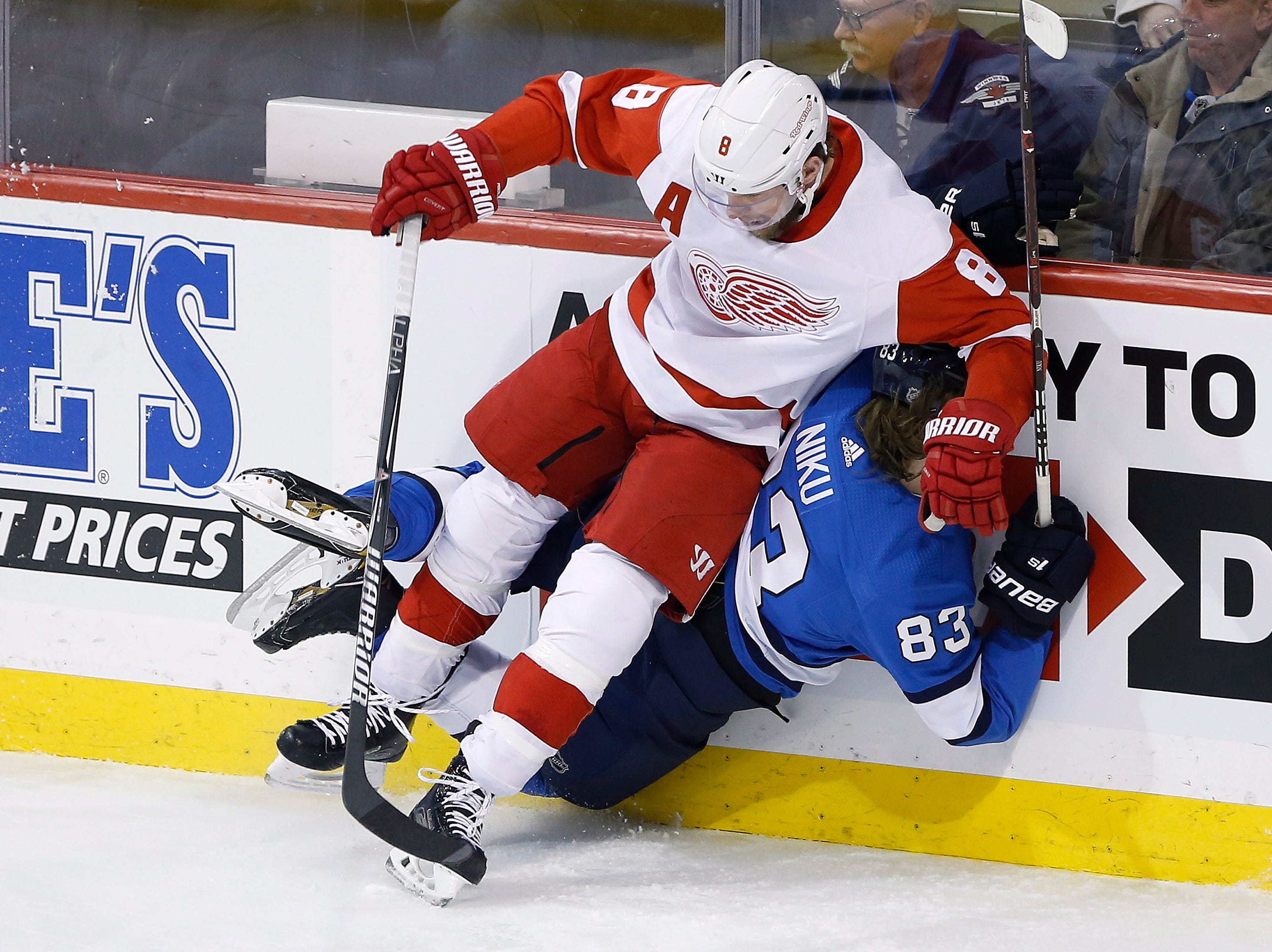 Winnipeg Jets' Sami Niku (83) is checked by Detroit Red Wings' Justin Abdelkader (8) during the first period.