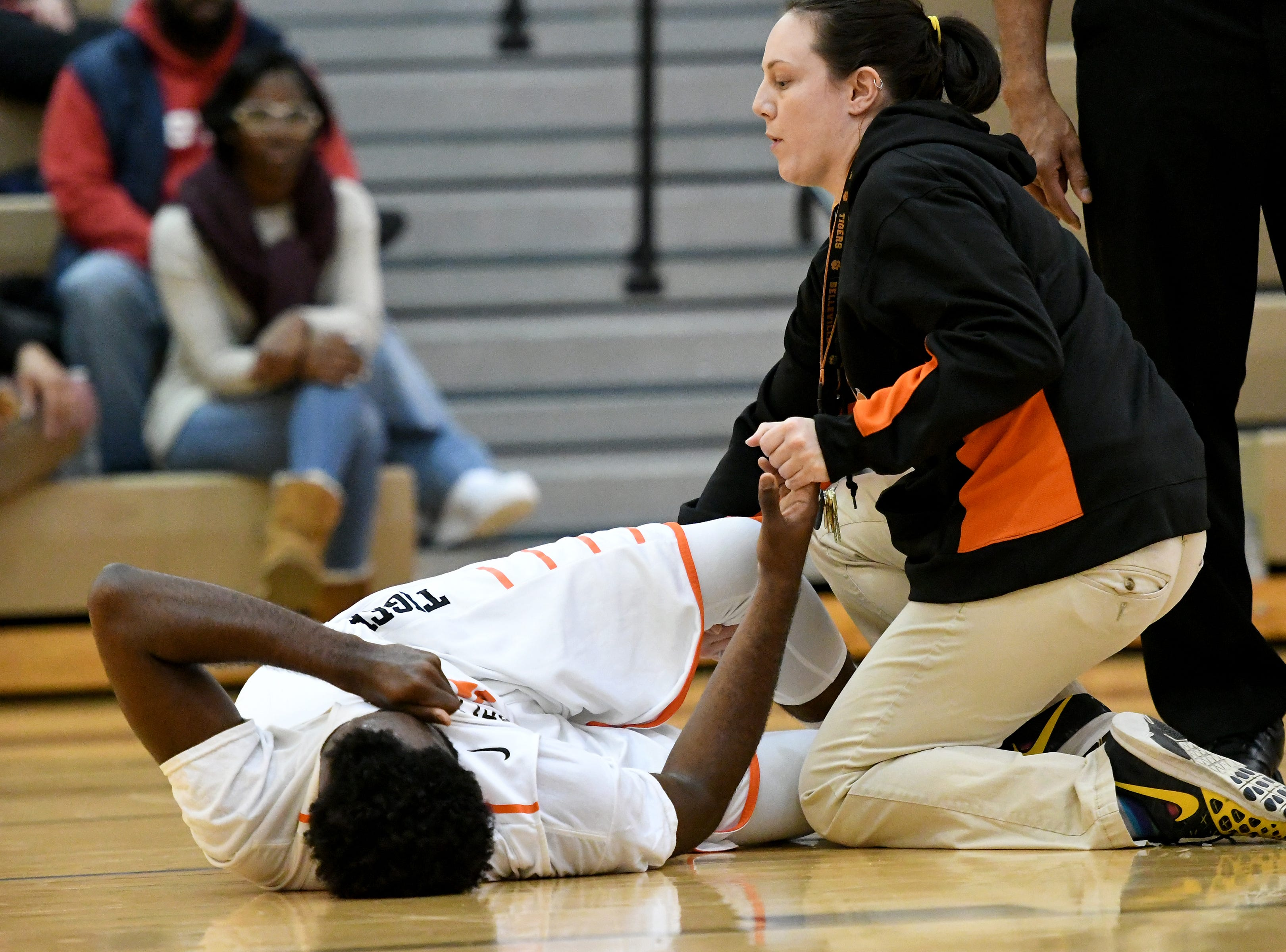 Belleville High School's Connor Bush grimaces in pain after hurting his leg driving to the hoop in the second quarter.