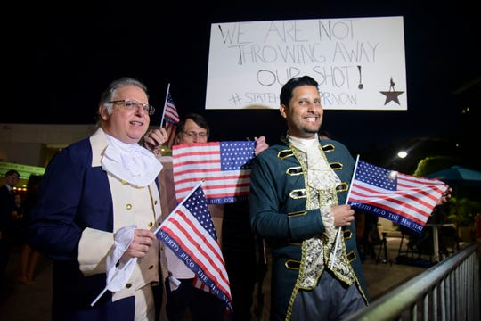 Dan Santiago, right, and Miguel Gallo, left, hold a demonstration in favor of statehood at the entrance plaza of the Santurce Fine Arts Center in San Juan, Puerto Rico.