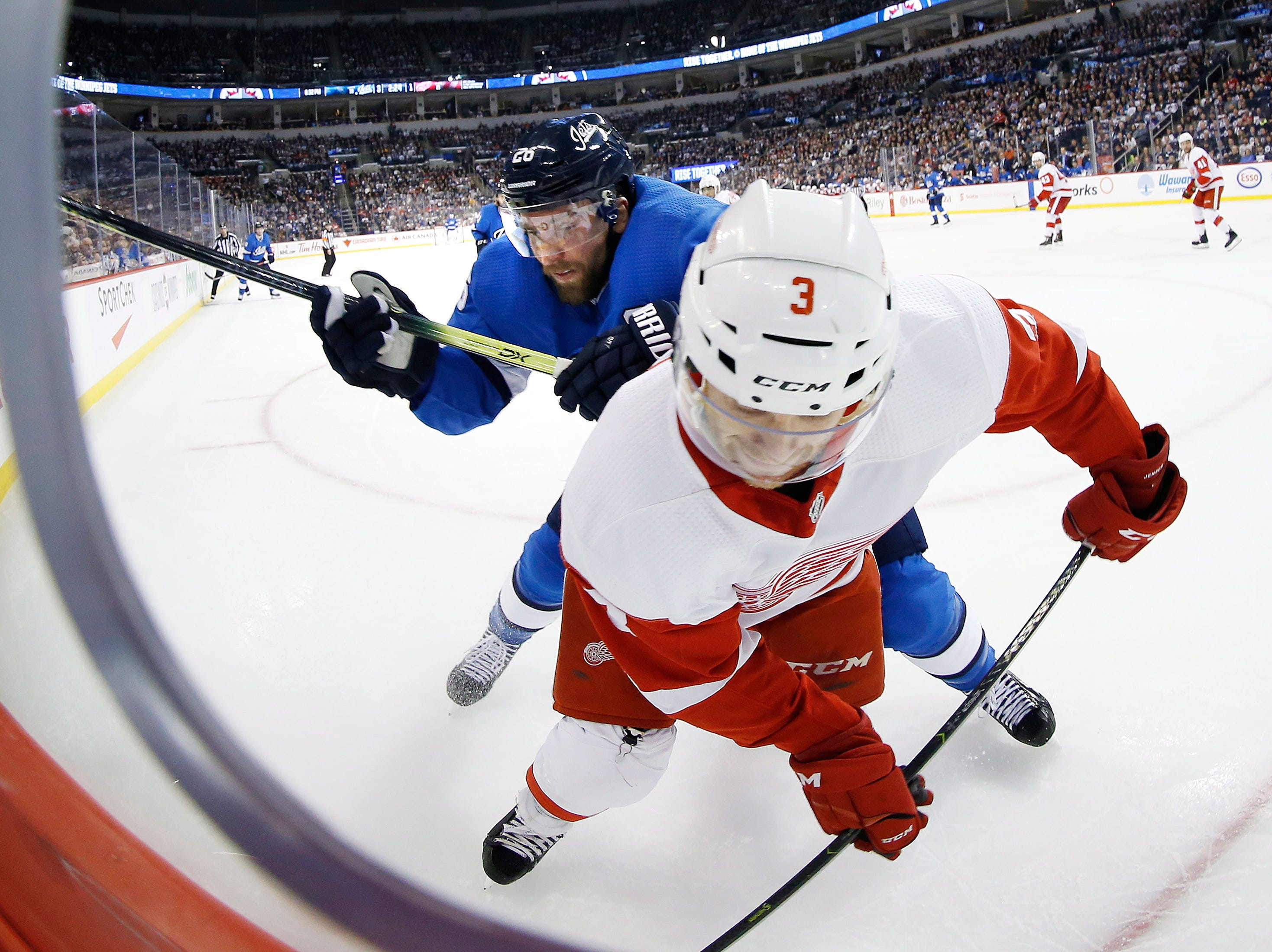 Winnipeg Jets' Jack Roslovic (28) checks Detroit Red Wings' Nick Jensen (3) during the second period.