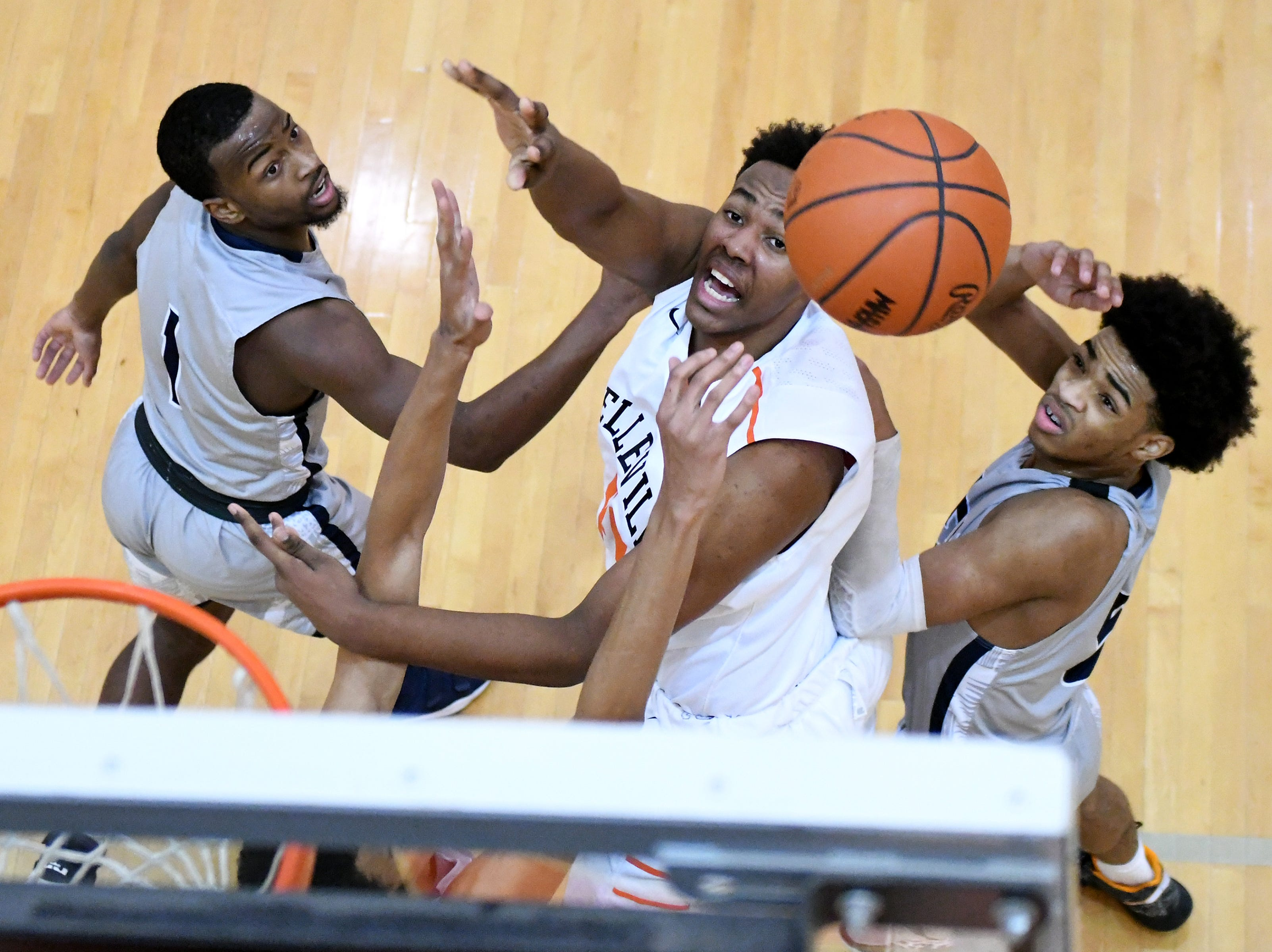 Belleville High School's Brandon Jackson, center, battles for a rebound with John Glenn High School's Elijah White, left, and Renel Thrasher Jr. right, during the first quarter at Belleville High School, January 11, 2019.