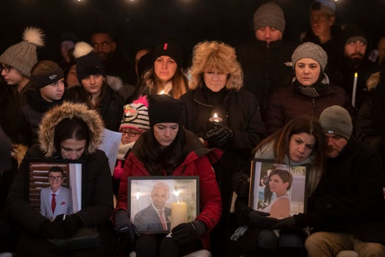 At a January vigil in Northville, family members hold pictures of the Abbas family who were killed in a traffic accident in Kentucky.