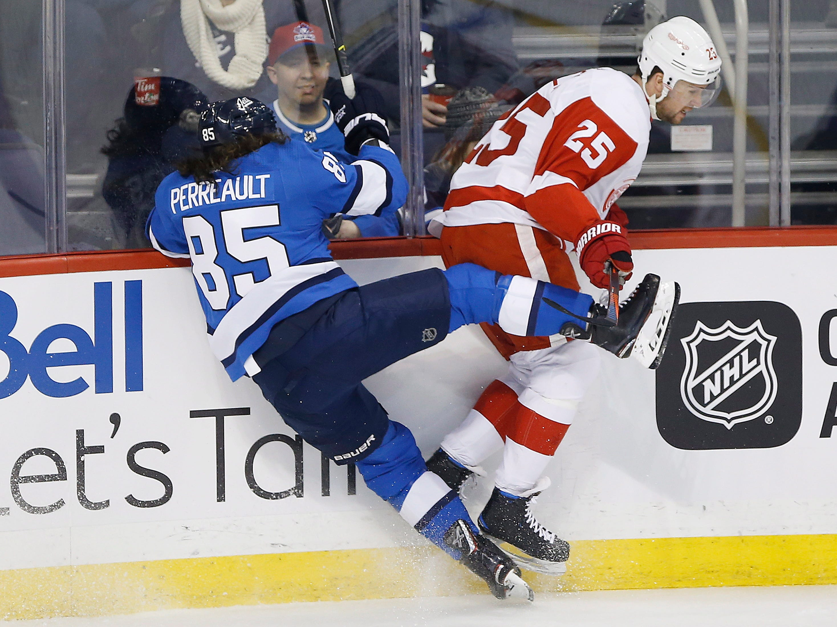 Winnipeg Jets' Mathieu Perreault (85) and Detroit Red Wings' Mike Green (25) collide during the first period.