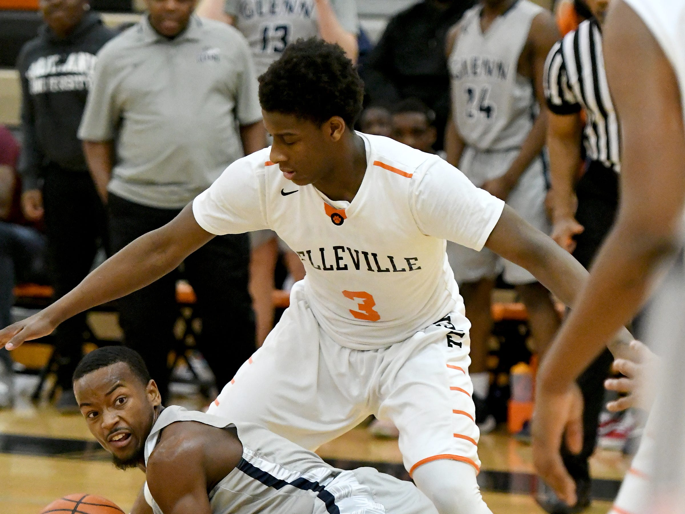 John Glenn High School's Elijah White, bottom, tries to pass to a teammate while falling to the court while being defended by Belleville High School's, Jalen Williams in the fourth quarter.