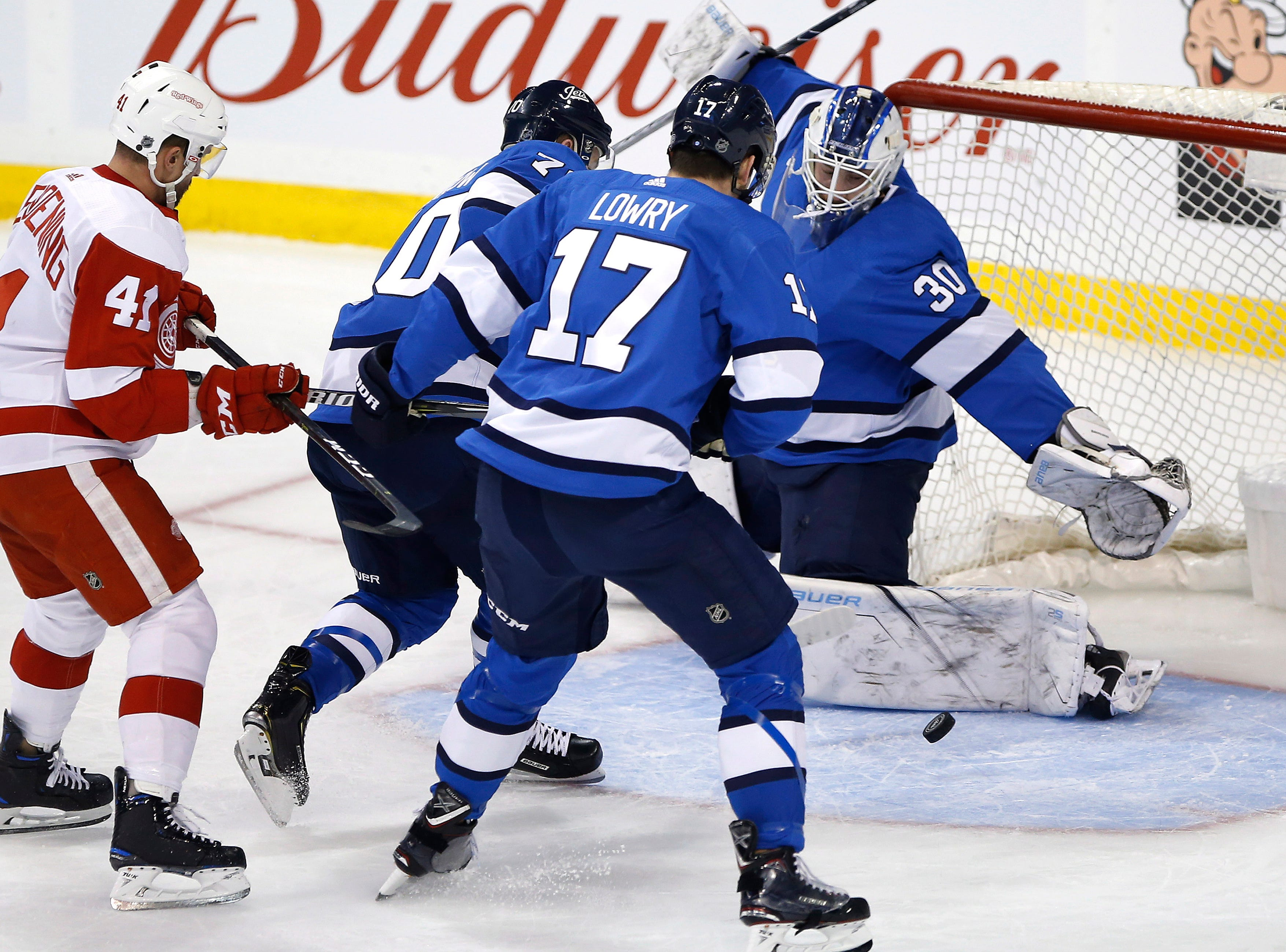 Winnipeg Jets goaltender Laurent Brossoit (30) makes the save on a shot by Detroit Red Wings' Luke Glendening (41) as Jets' Joe Morrow (70) and Adam Lowry (17) defend during first period.