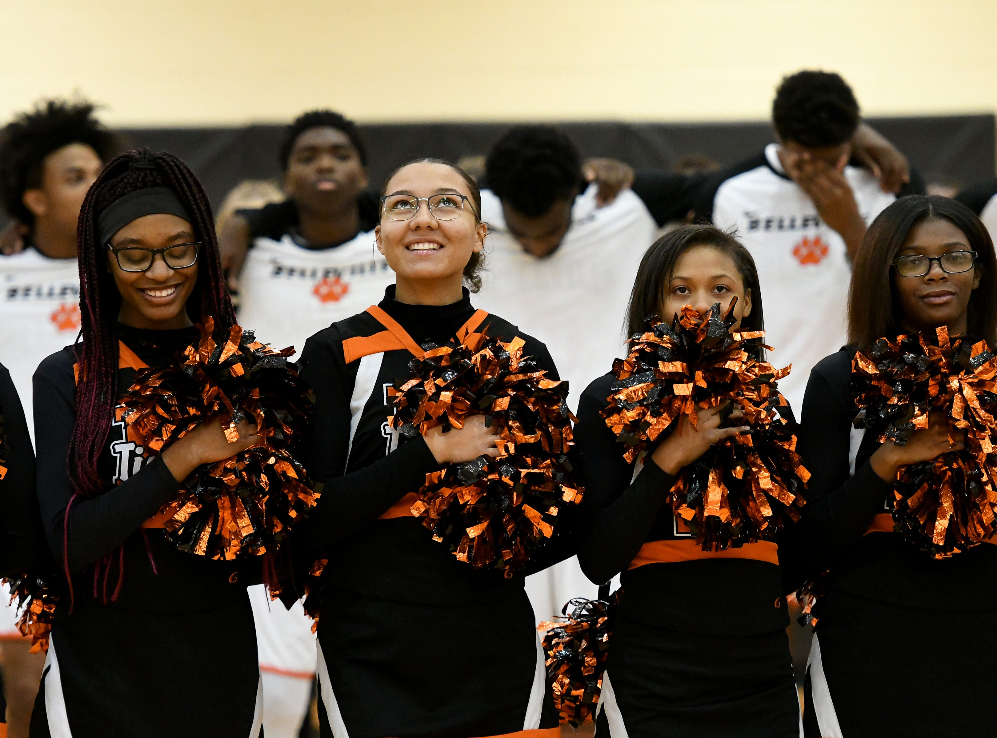 Belleville High School cheerleaders and players stand at attention for the National Anthem before their game with John Glenn High School.