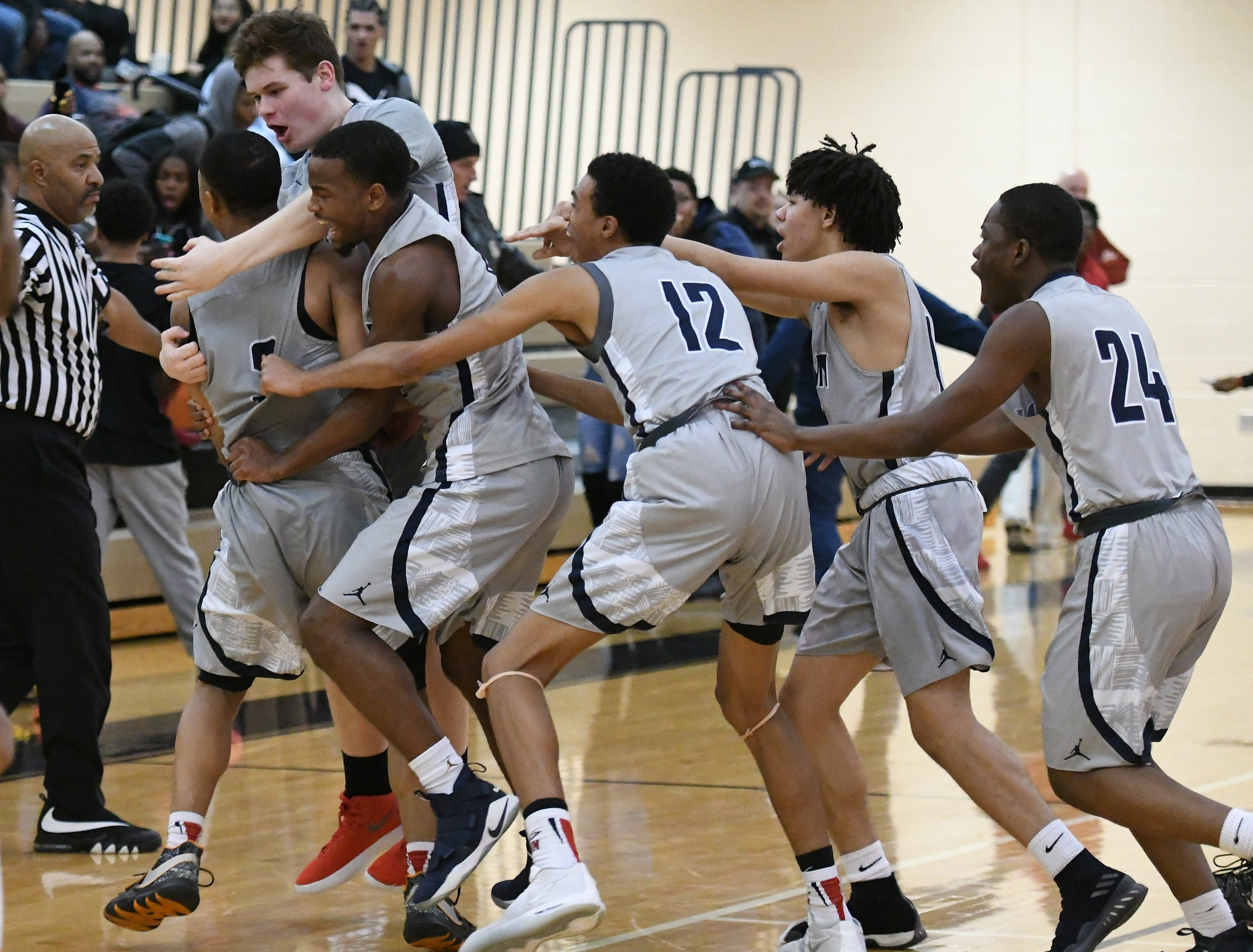 John Glenn High School's Joe Moon IV, far left, is mobbed by his teammate after hitting a three pointer at the end of regulation to send their game against Belleville High School into overtime. Moon would score 43 points on the night, but it wouldn't be enough to beat Belleville, who escaped with a 81-78 win.