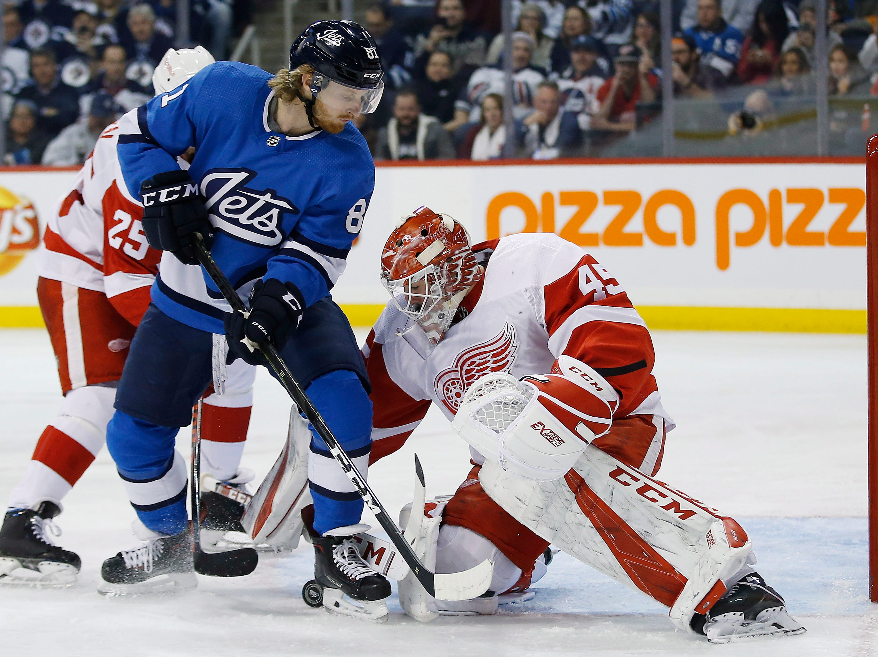 Detroit Red Wings goaltender Jonathan Bernier (45) jumps on a loose puck as Winnipeg Jets' Kyle Connor (81) applies pressure and Wings' Mike Green (25) defends during the second period.