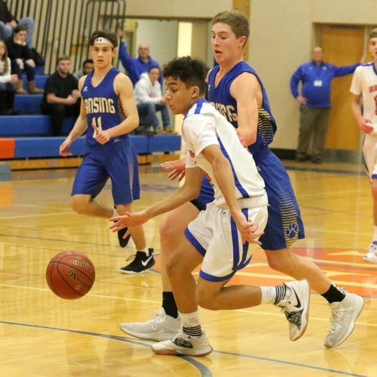 Noah Jeronimo of Thomas A. Edison dribbles up the court in front of Lansing's Ethan Burt in boys basketball Jan. 11, 2019 in Elmira Heights.
