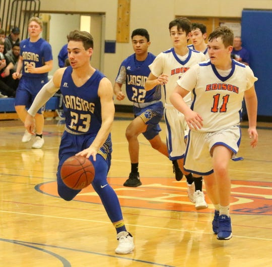 Garrett Bell dribbles the ball up the court for Lansing as Jack Hourihan of Thomas A. Edison gives chase during boys basketball Jan. 11, 2019 in Elmira Heights.