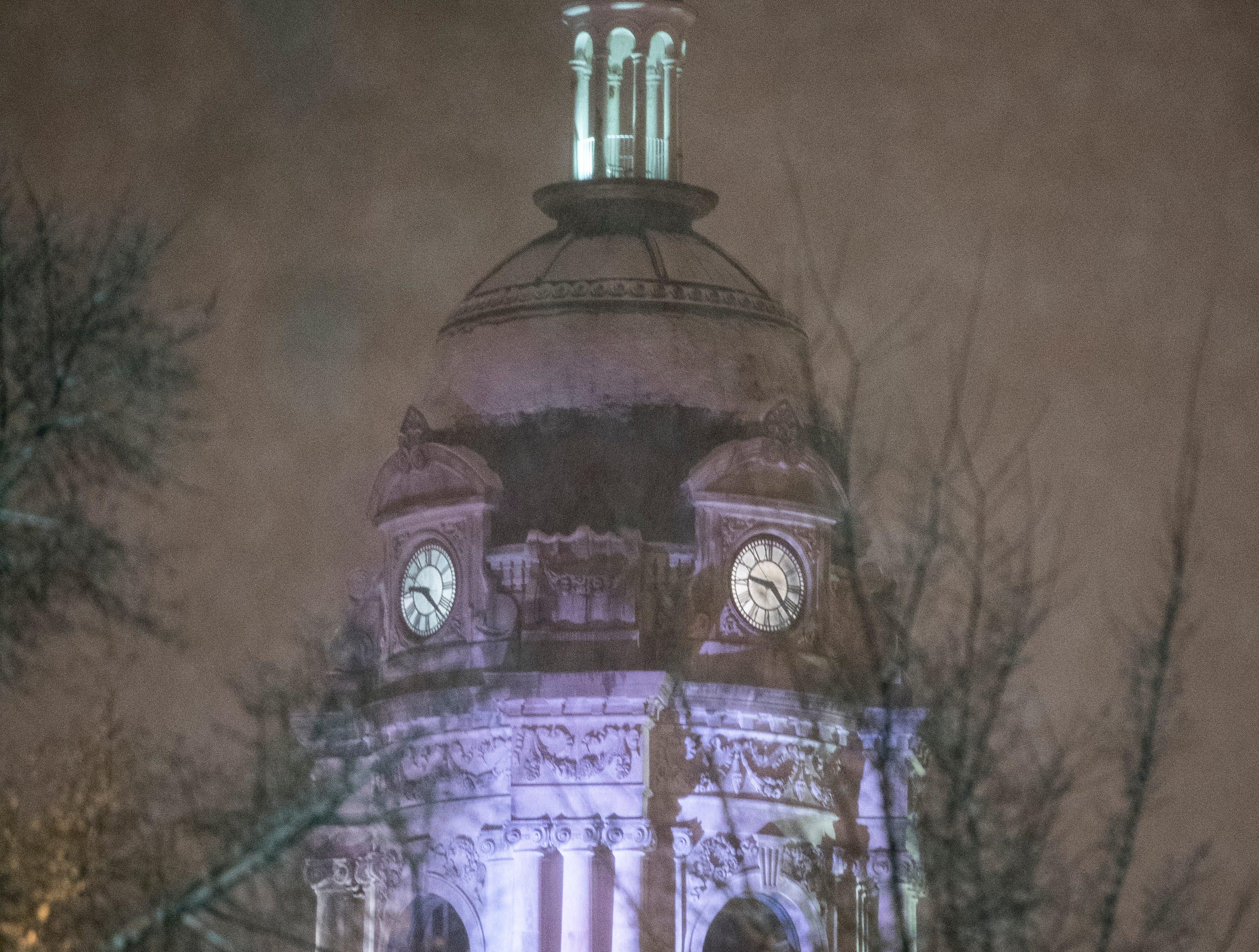 The top of the Old Court House in Downtown Evansville glows purple as snow beings to accumulate on the dome Friday evening Jan. 11, 2019.