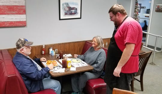 "Employee James Pryor chats with regular customers Brenda Riggs and Roger Nunn.  ""The service is good and the food is good and they make you feel at home,"""