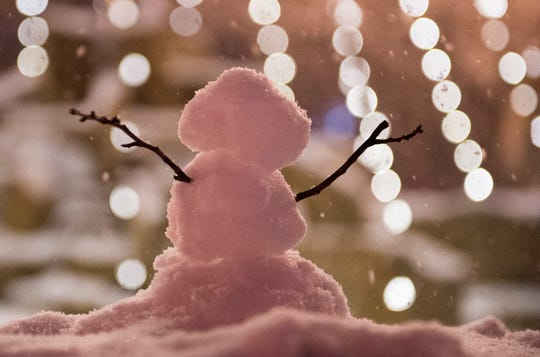 A miniature snowman sits in front of the fountain on Haynie's Corner as snow continues to fall Friday evening Jan. 11, 2019.