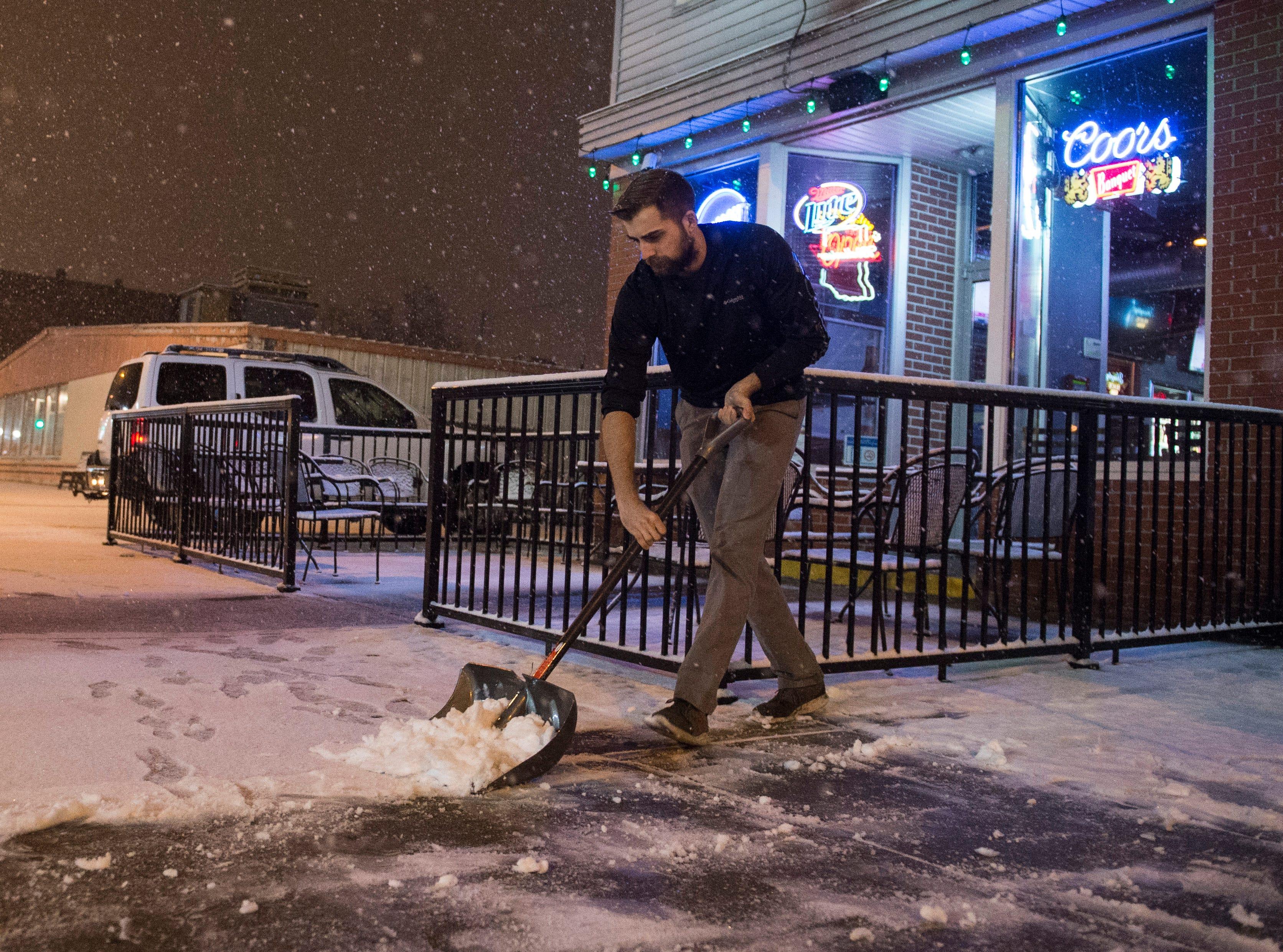 Bartender at Franklin Street Tavern Dylan Winkler shovels the sidewalk as snow begins to accumulate Friday evening Jan. 11, 2019.