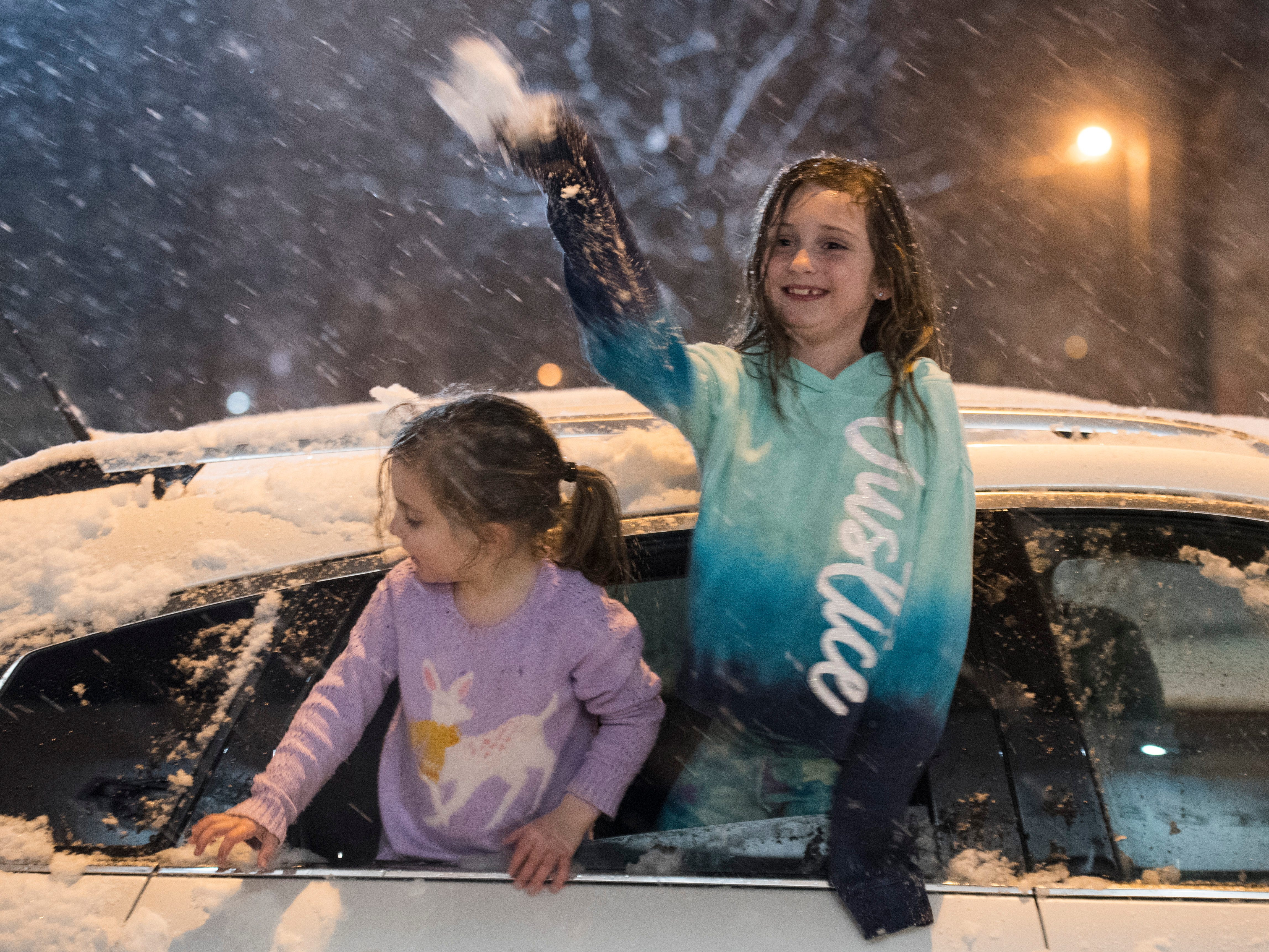 Scarlet, left, and Savannah Denton throw snowballs at their dad after ice cream at Milk and Sugar Scoop Shoppe on West Franklin Street Friday, Jan. 11, 2019.