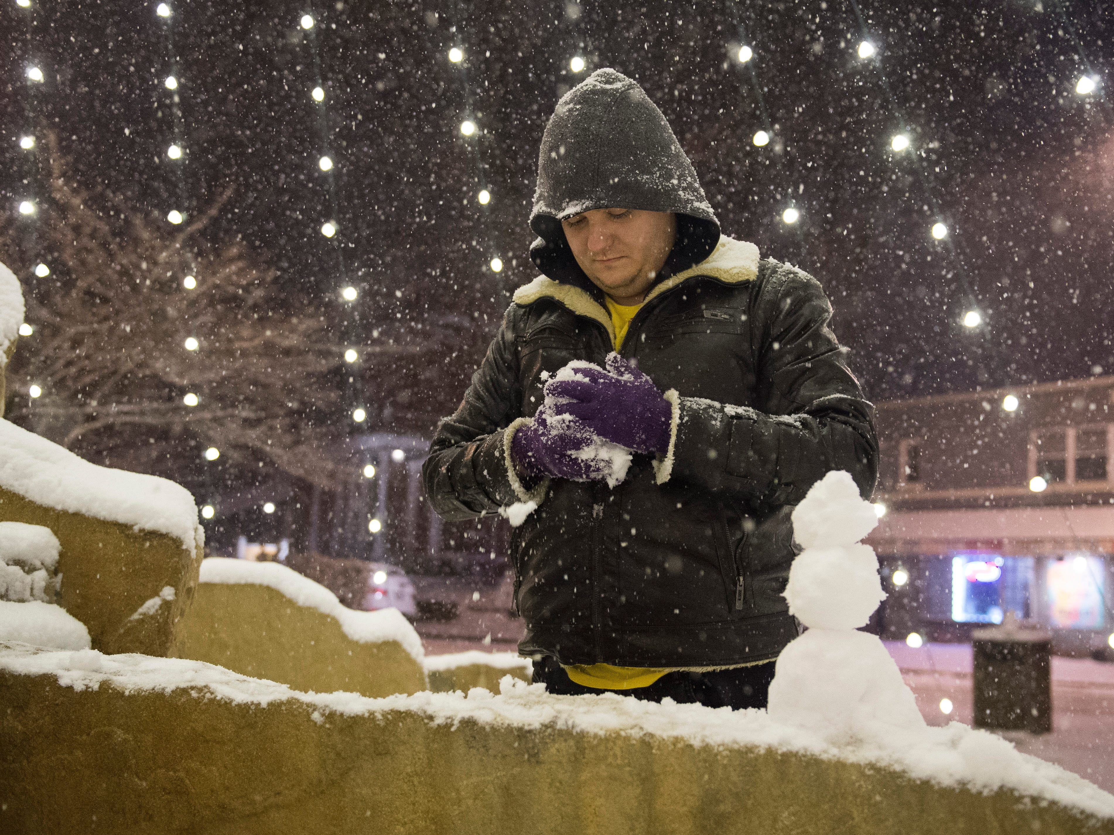 Haynie's Corner resident Cody Poole makes miniature snowmen on the fountain as snow continues to fall Friday evening Jan. 11, 2019.
