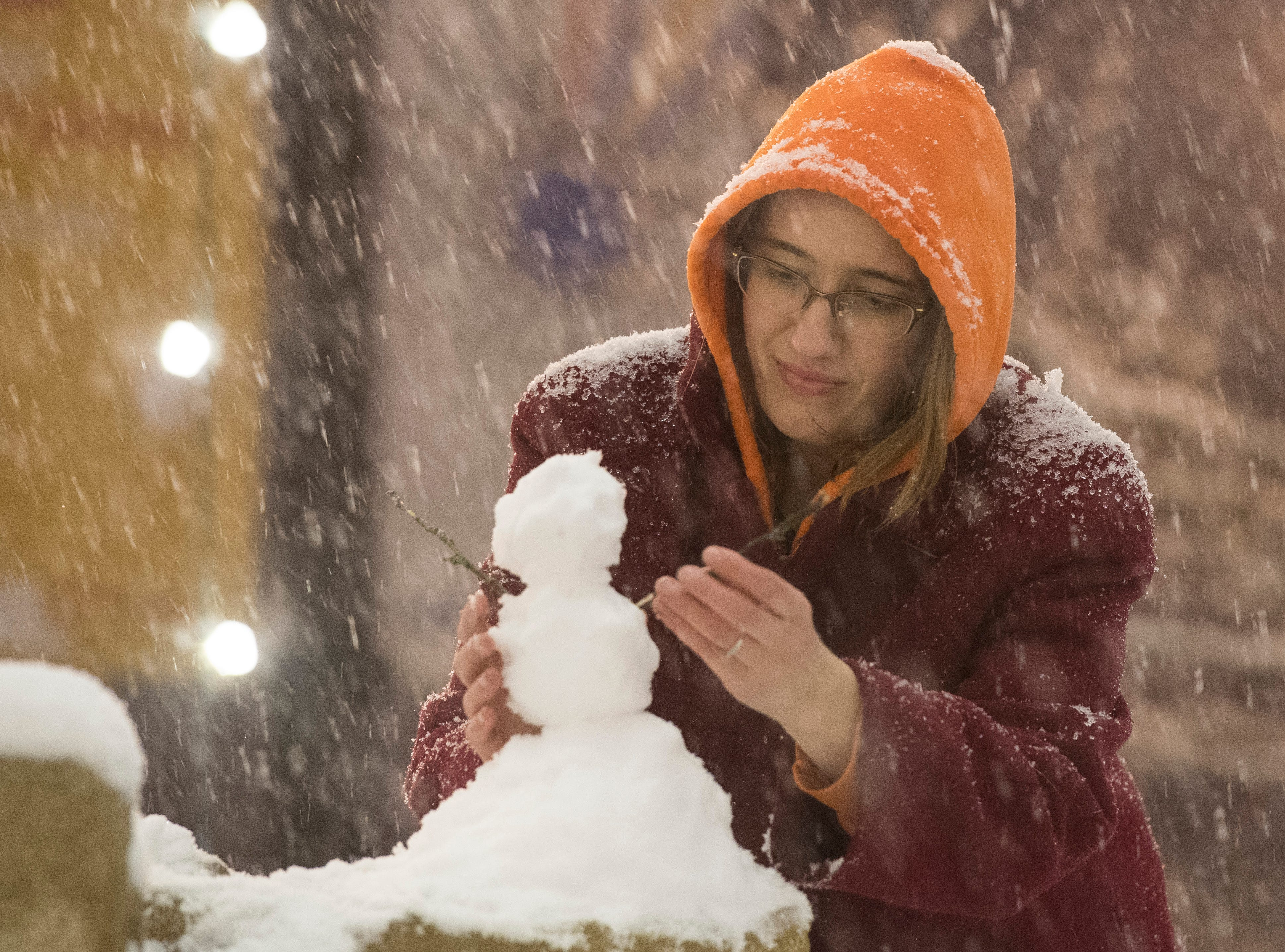 Haynie's Corner resident Kellsie Phillips adds arms to a miniature snowmen that sits on the fountain as snow continues to fall Friday evening Jan. 11, 2019.