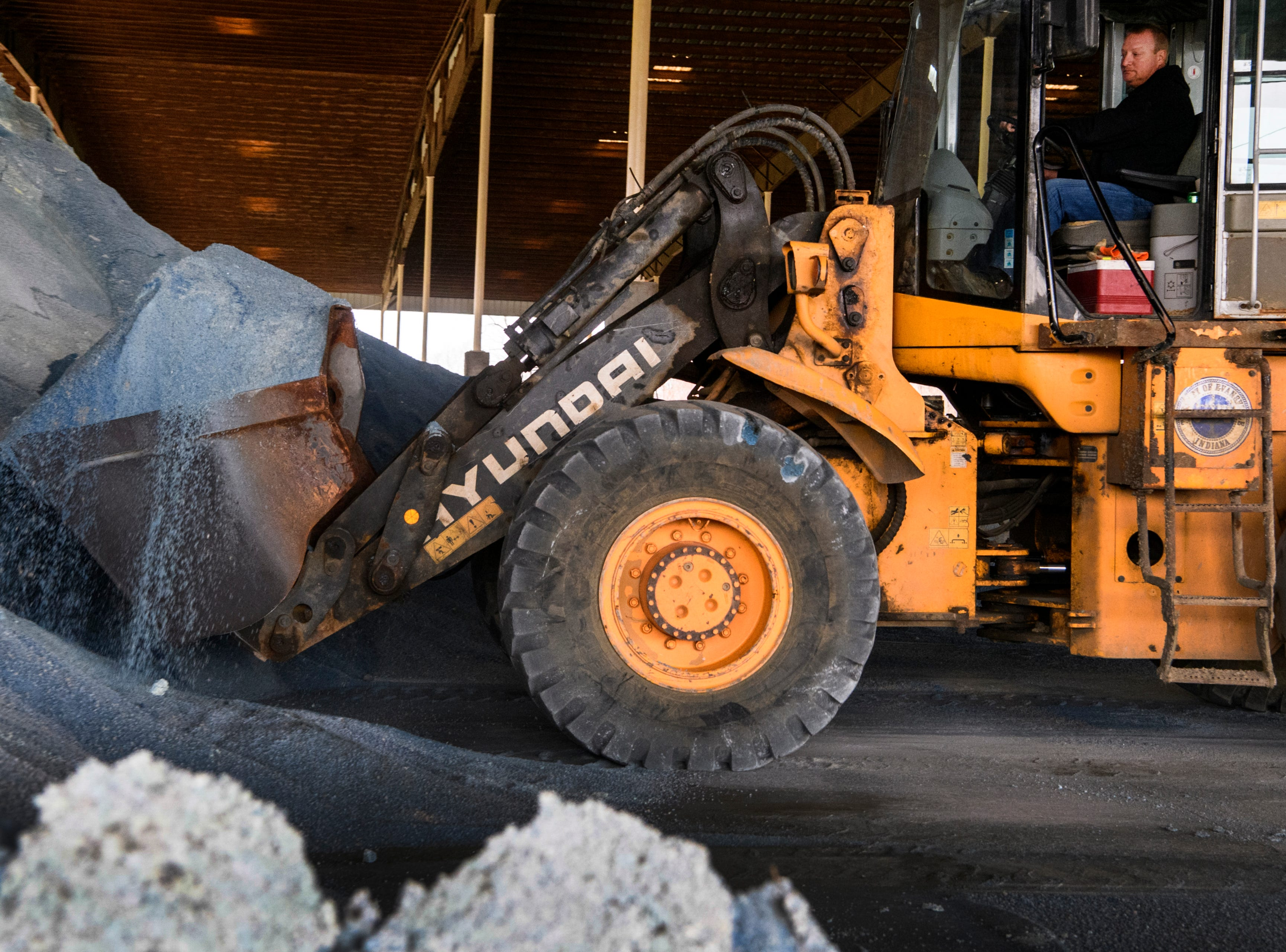 Brad Haller, a City of Evansville's Street Maintenance operator, scoops up salt to load into a truck at the salt barn located in the East Waste Water Treatment plant in Evansville, Ind., Friday, Jan. 11, 2019. The city has twelve trucks that will be deployed around the area to treat roads as the weather worsens.