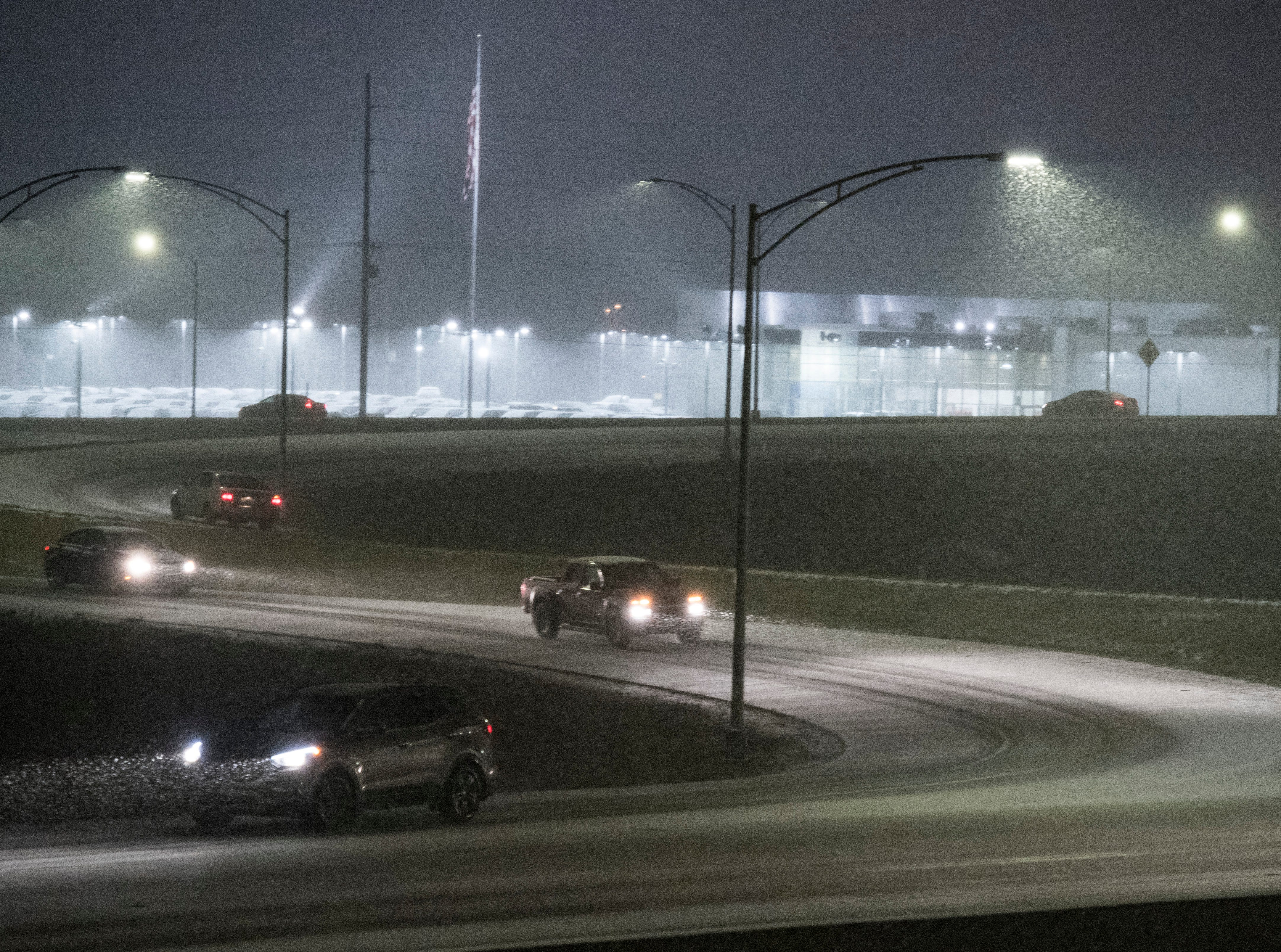 Vehicles drive slow while using the cloverleaf at U.S. 41 and the Lloyd Expressway as snow begins to accumulate on the road Friday evening Jan. 11, 2019.
