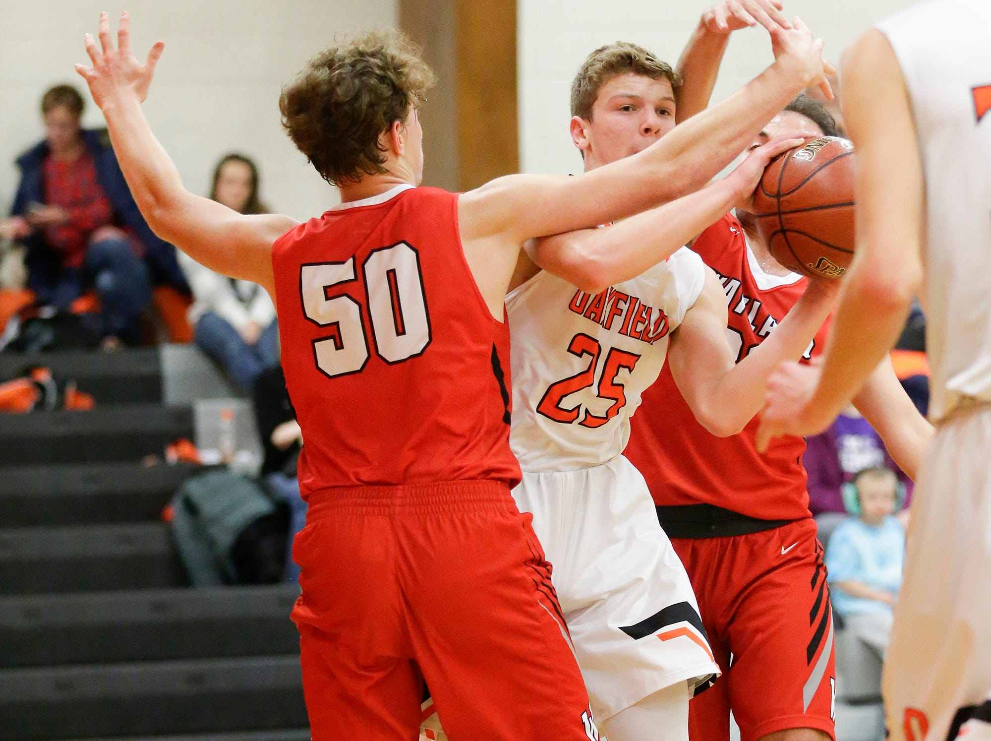Oakfield High School boys basketball's Grant Bass attempts to pass the ball away from Wayland Academy's Adam Rubinchik (50) and Kerem Kocer (30) January 11, 2019 during their game in Oakfield. Oakfield won the game 56-48. Doug Raflik/USA TODAY NETWORK-Wisconsin