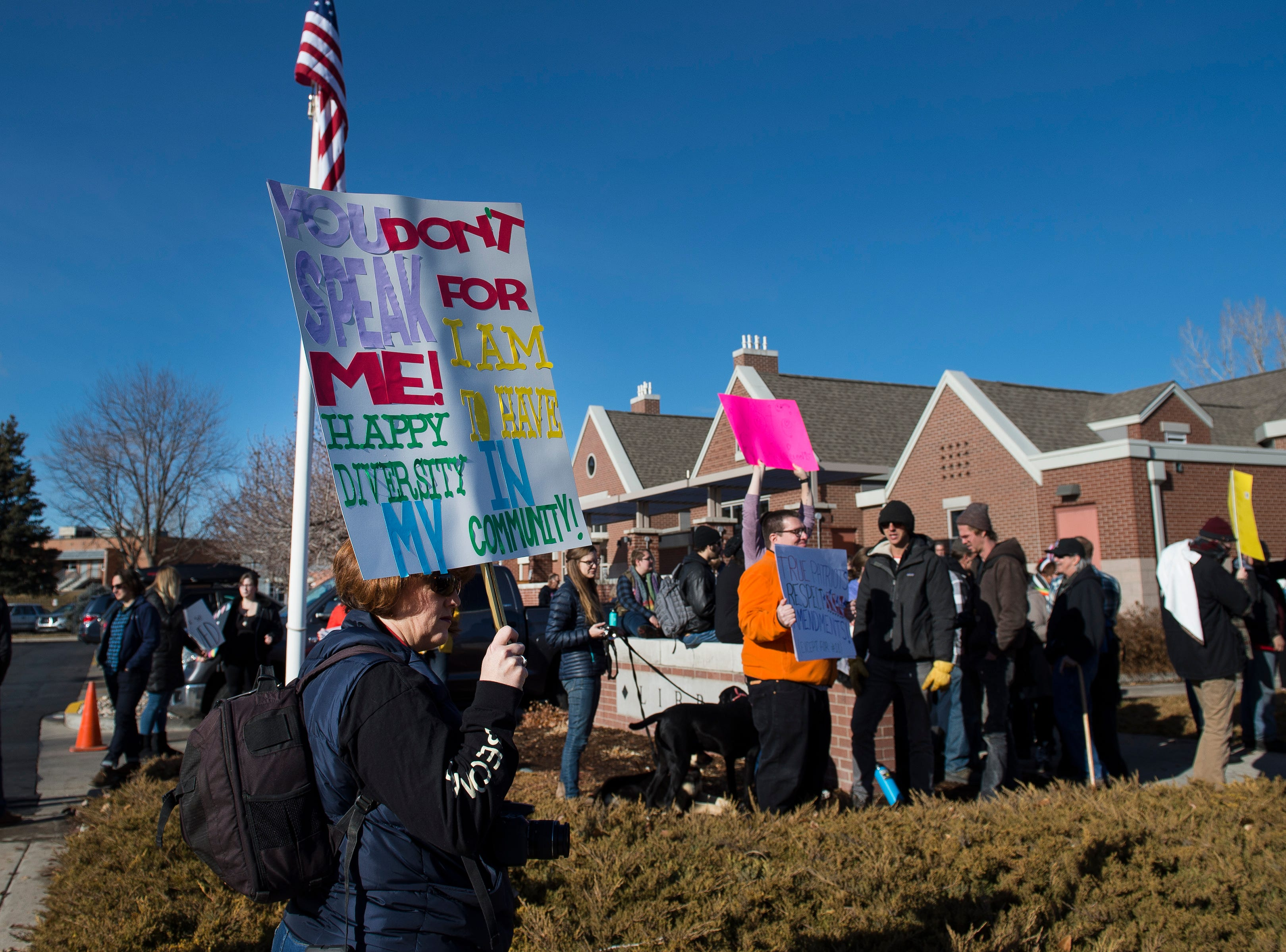 Kim Grubbs holds up a sign while protesters and counterprotesters gather outside the library before Drag Queen Story Hour on Saturday, Jan. 12, 2019, at the Clearview Public Library in Windsor, Colo. Drag Queen Story Hour is a program put on by SPLASH, an LGBTQ+ youth outreach organization.