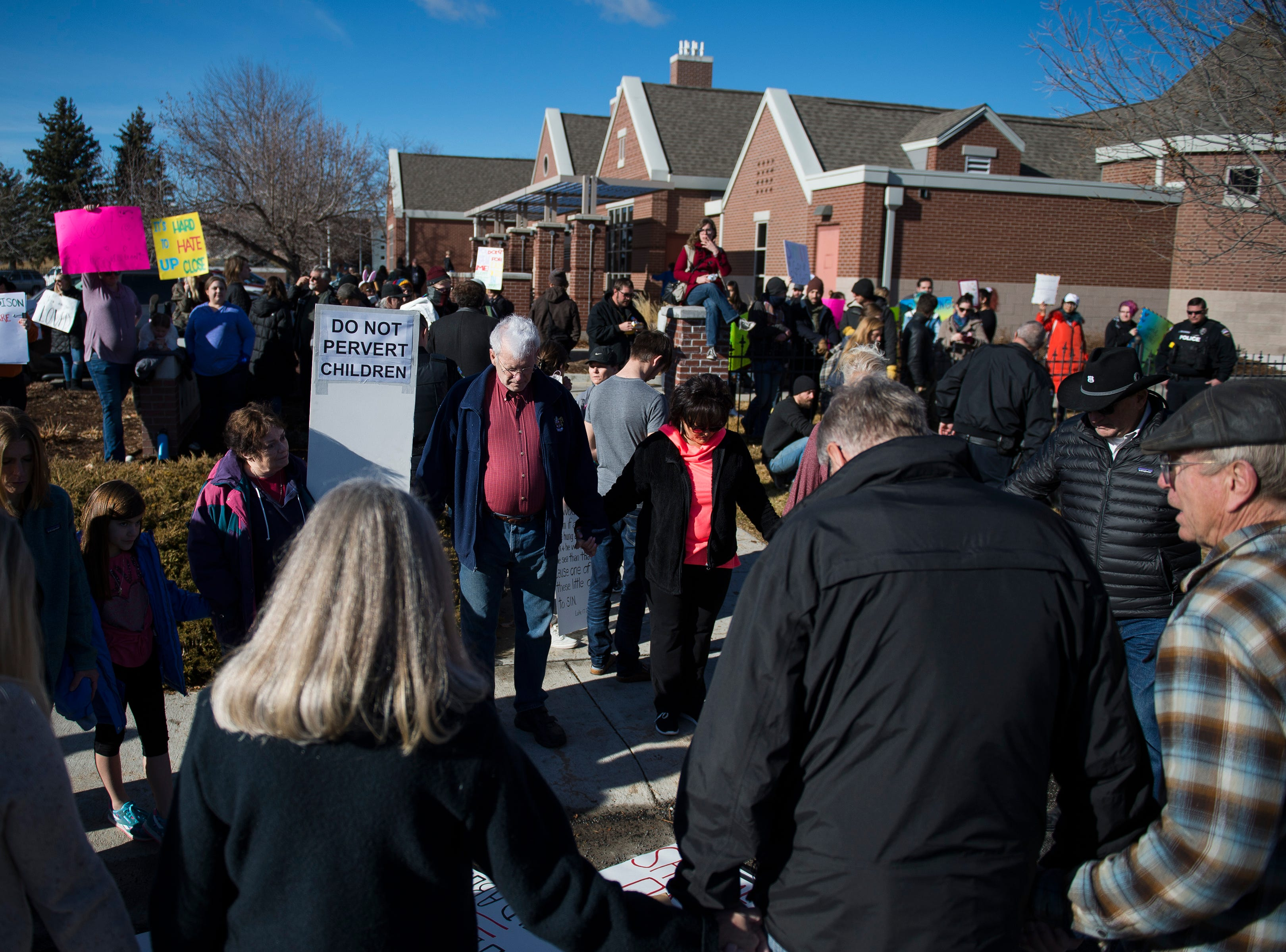 A group of protesters stand in a circle and pray outside the library before Drag Queen Story Hour on Saturday, Jan. 12, 2019, at the Clearview Public Library in Windsor, Colo. Drag Queen Story Hour is a program put on by SPLASH, an LGBTQ+ youth outreach organization.