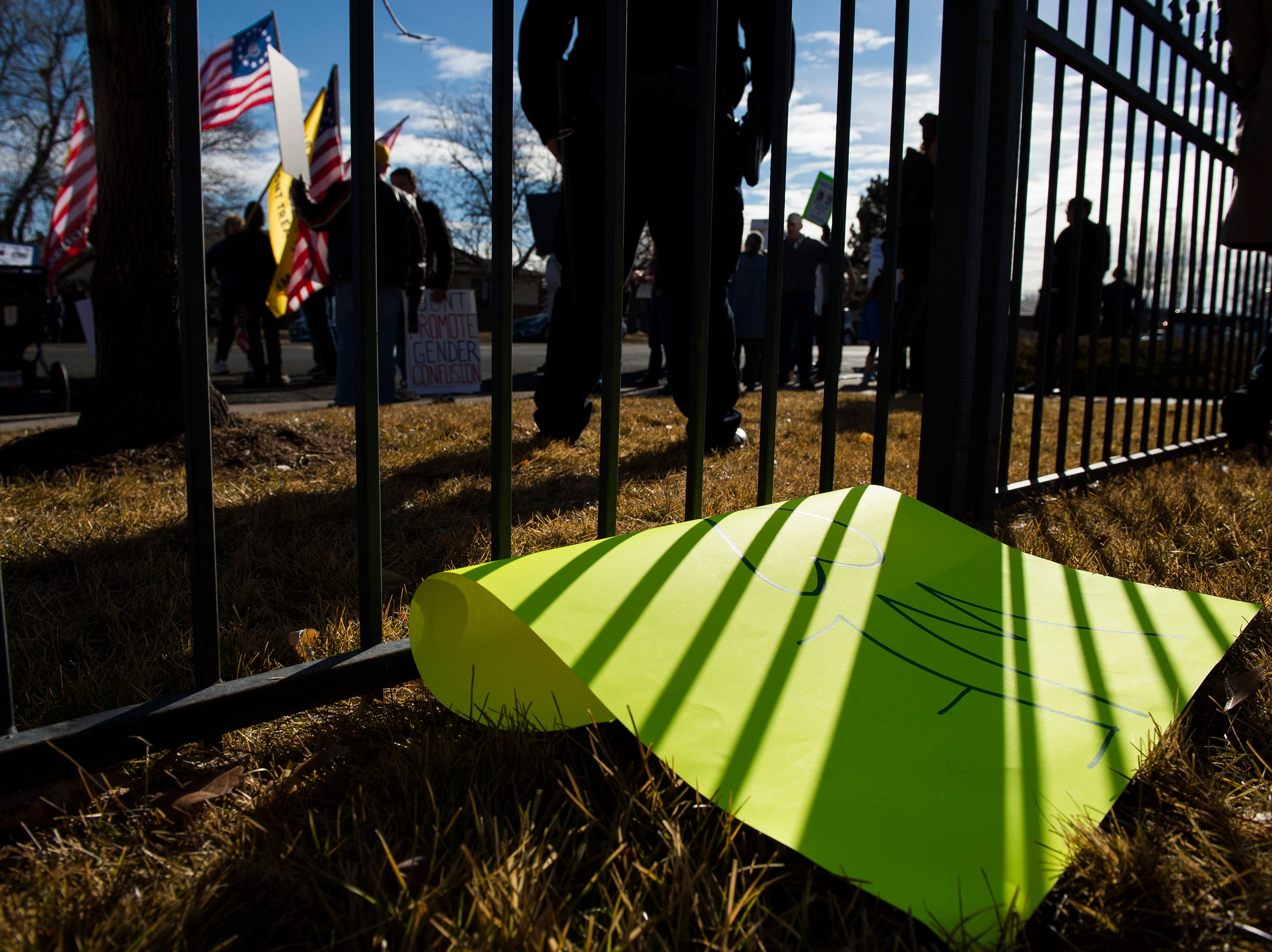 A counterprotester's sign sits in the grass while protestors gather outside the library before Drag Queen Story Hour on Saturday, Jan. 12, 2019, at the Clearview Public Library in Windsor, Colo. Drag Queen Story Hour is a program put on by SPLASH, an LGBTQ+ youth outreach organization.