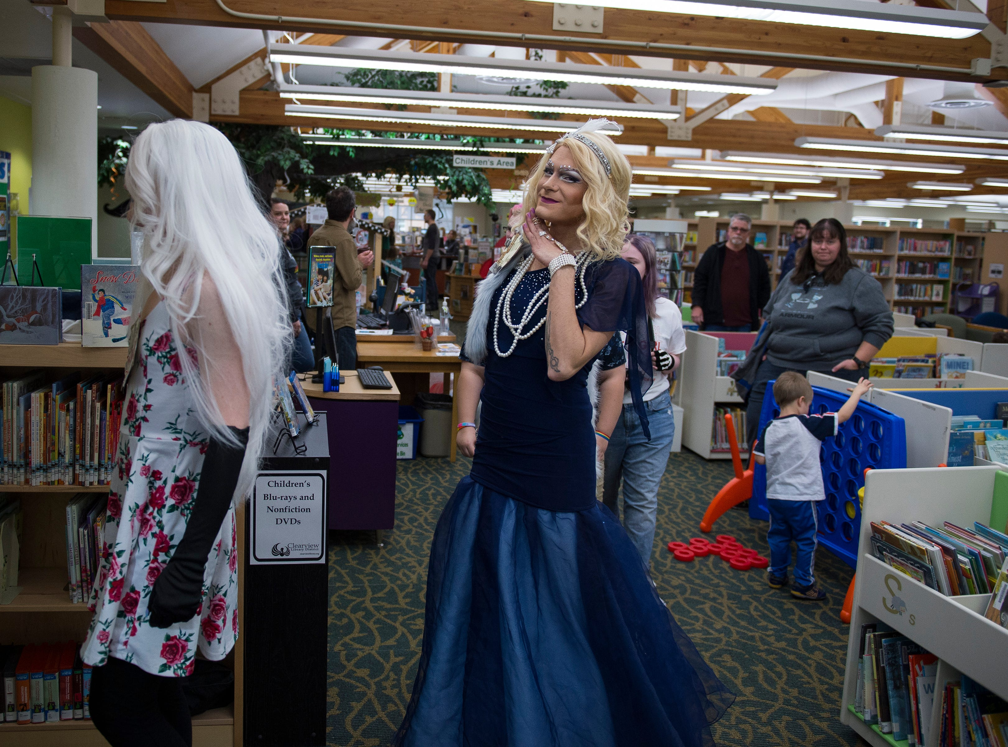 Drag queen Unita ReadMoore poses for the camera while she, Miss Mayyhem, left, and drag king Simon Hyperion head to the private room for Drag Queen Story Hour on Saturday, Jan. 12, 2019, at the Clearview Public Library in Windsor, Colo. Drag Queen Story Hour is a program put on by SPLASH, an LGBTQ+ youth outreach organization.