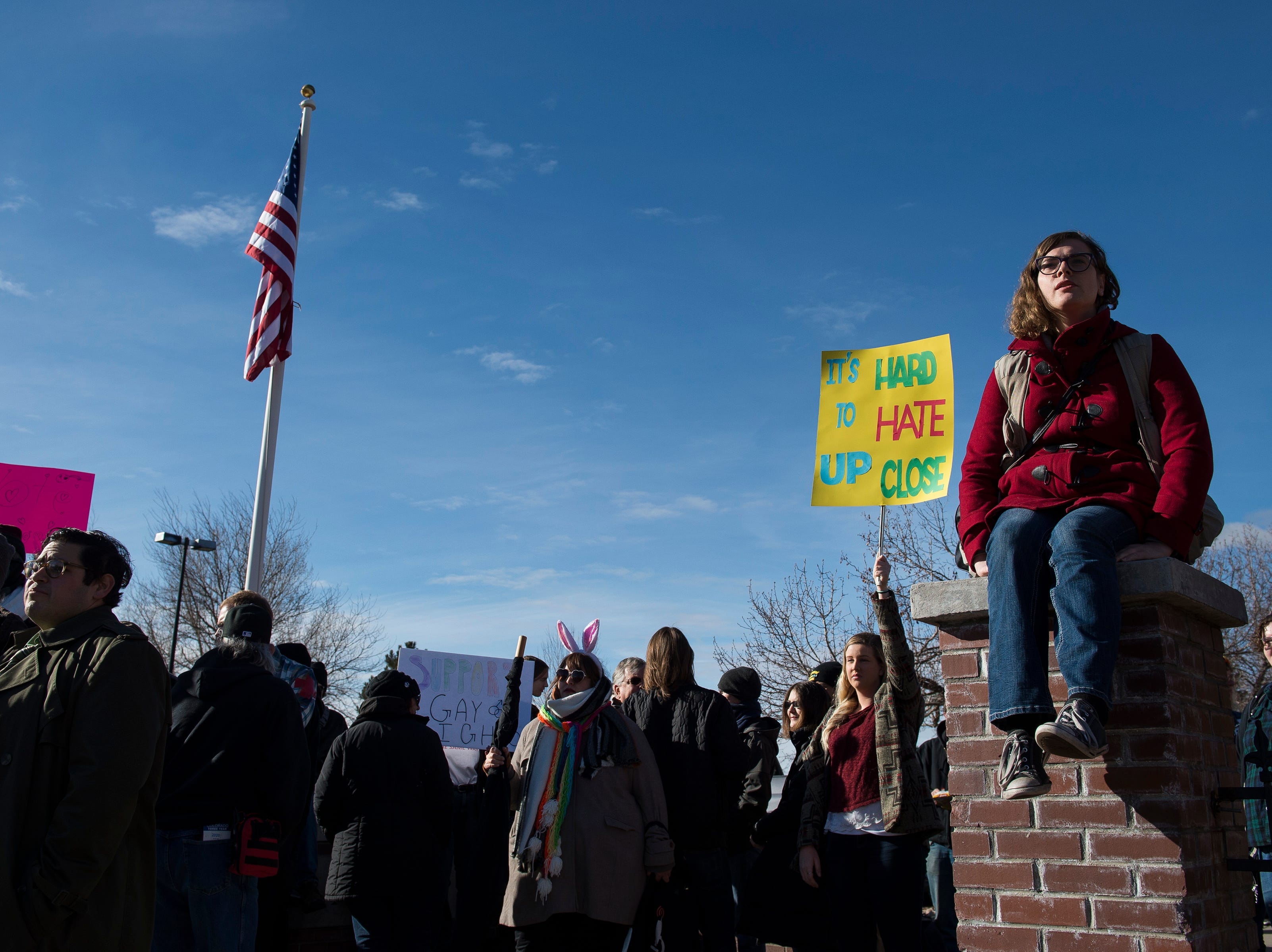 Counterprotester Violet Valentine sits on a gate while others gather outside the library before Drag Queen Story Hour on Saturday, Jan. 12, 2019, at the Clearview Public Library in Windsor, Colo. Drag Queen Story Hour is a program put on by SPLASH, an LGBTQ+ youth outreach organization.