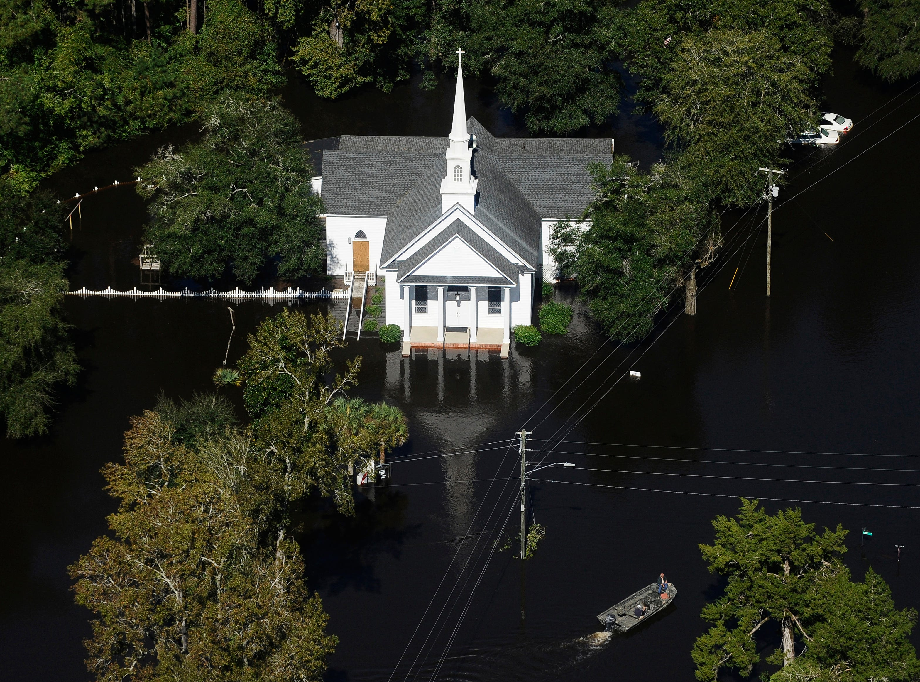 A boat passes a submerged church in Nichols Oct. 10, 2016. Nearly 1 million homes and businesses still did not have power that day in the Carolinas after Hurricane Matthew.