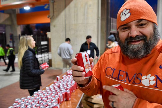 Chris Matney of Lugoff, SC,  holds one of the Clemson National Championship Coke cans given to first 2,400 at Memorial Stadium on Saturday.
