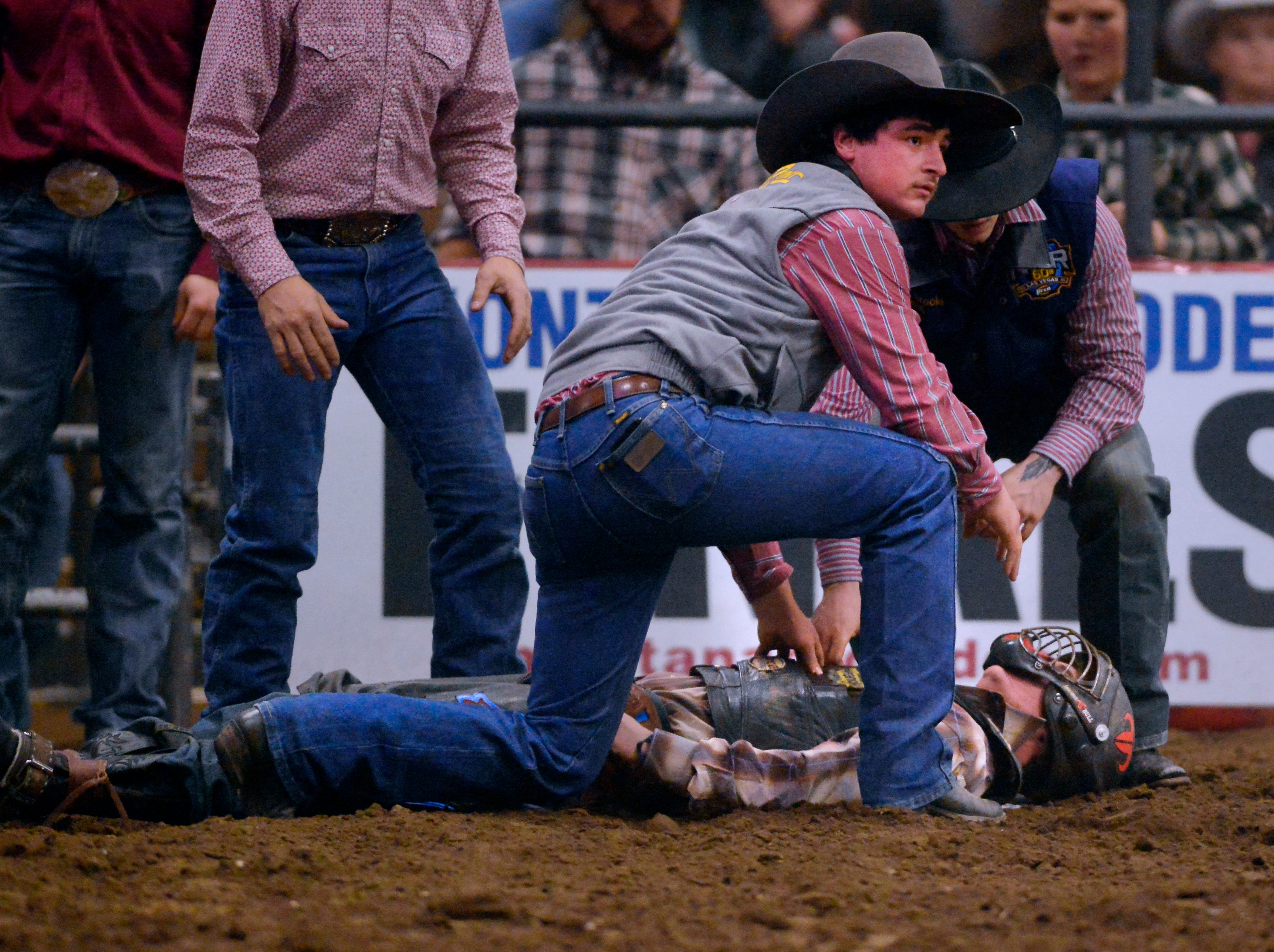 Other riders run to the aid of Devon Mitchell who was knocked unconscious on his ride in the bull riding event during the Montana Pro Rodeo Circuit Finals in the Pacific Steel and Recycling Four Seasons Arena, Friday, January 11, 2019.