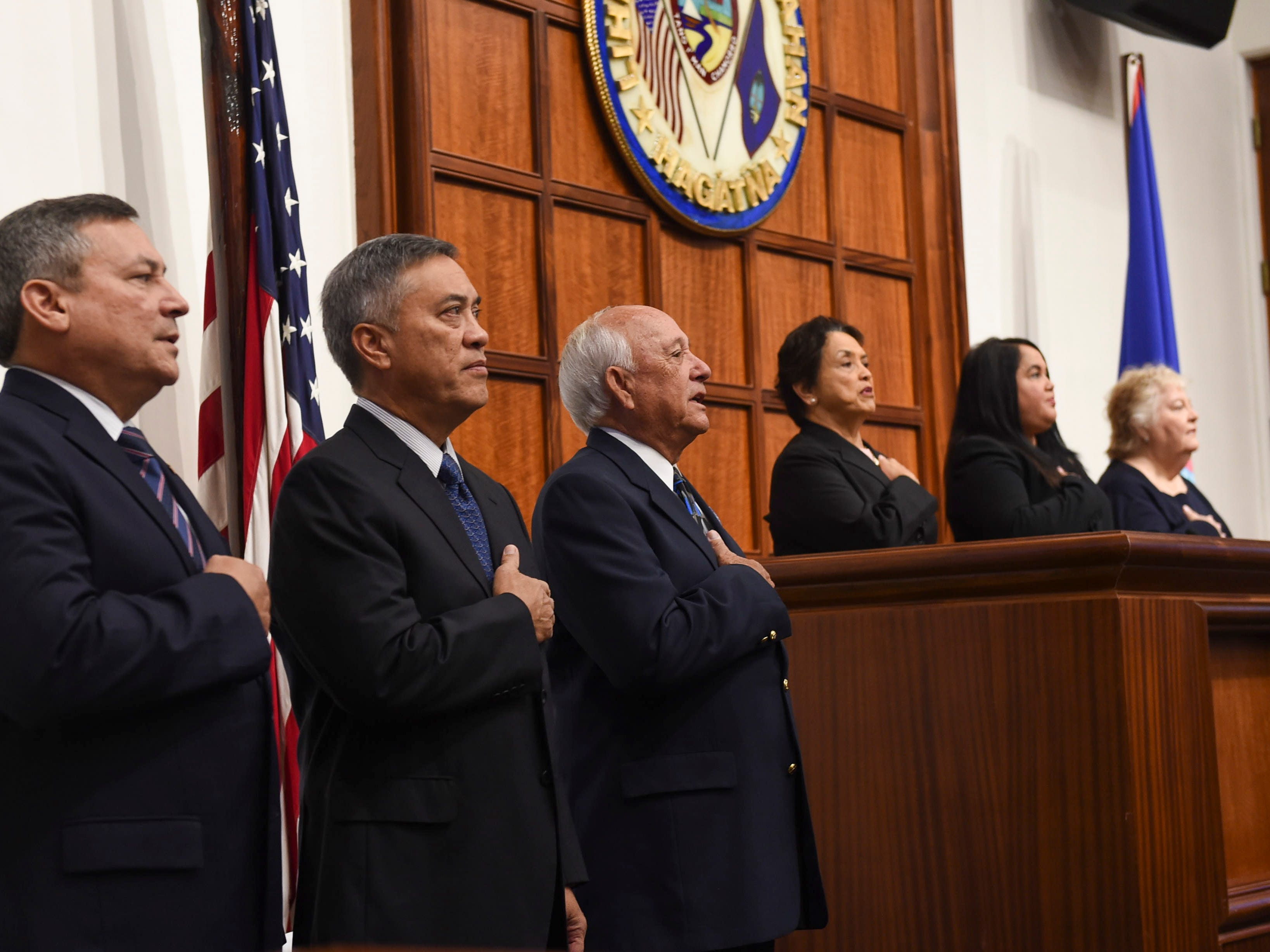 "Dignitaries stand at attention for the national anthem during the state memorial service of former Piti Mayor Vicente ""Ben"" Gumataotao, at the Guam Congress Building on Jan. 12, 2019. From left: Former Govs. Eddie Baza Calvo, Felix Camacho, Carl T.C. Gutierrez, Gov. Lou Leon Guerrero, Speaker Tina Muna Barnes, and Chief Justice Katherine Maraman."