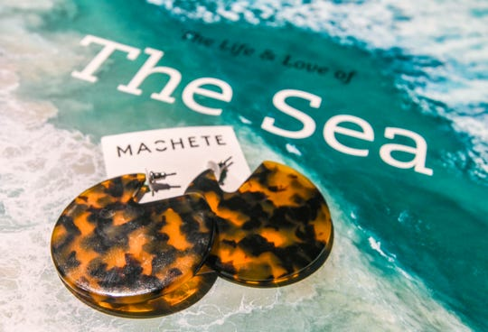 A resin tortoise shell-style pair of Machete brand earrings which can offer a nautical feel could be found at the Seas and Sidewalks store in the Micronesia Mall on Friday, Jan. 11, 2019. The business, which opened it's door to the public last year in November, features trendy casual outfits for men and women, clothing to enjoy the sea and surf, as well as a collection of water sport equipment.