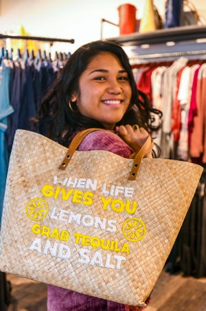 Ariana Andres; Fashion Designer, Fashion Merchandiser and CEO of the Seas and Sidewalks store at the Micronesia Mall, slings one of the many handbags that could be found at the family-operated store over her shoulder on Friday, Jan. 11, 2019. The business, which opened it's door to the public last year in November, features trendy casual outfits for men and women, clothing to enjoy the sea and surf, as well as a collection of water sport equipment.